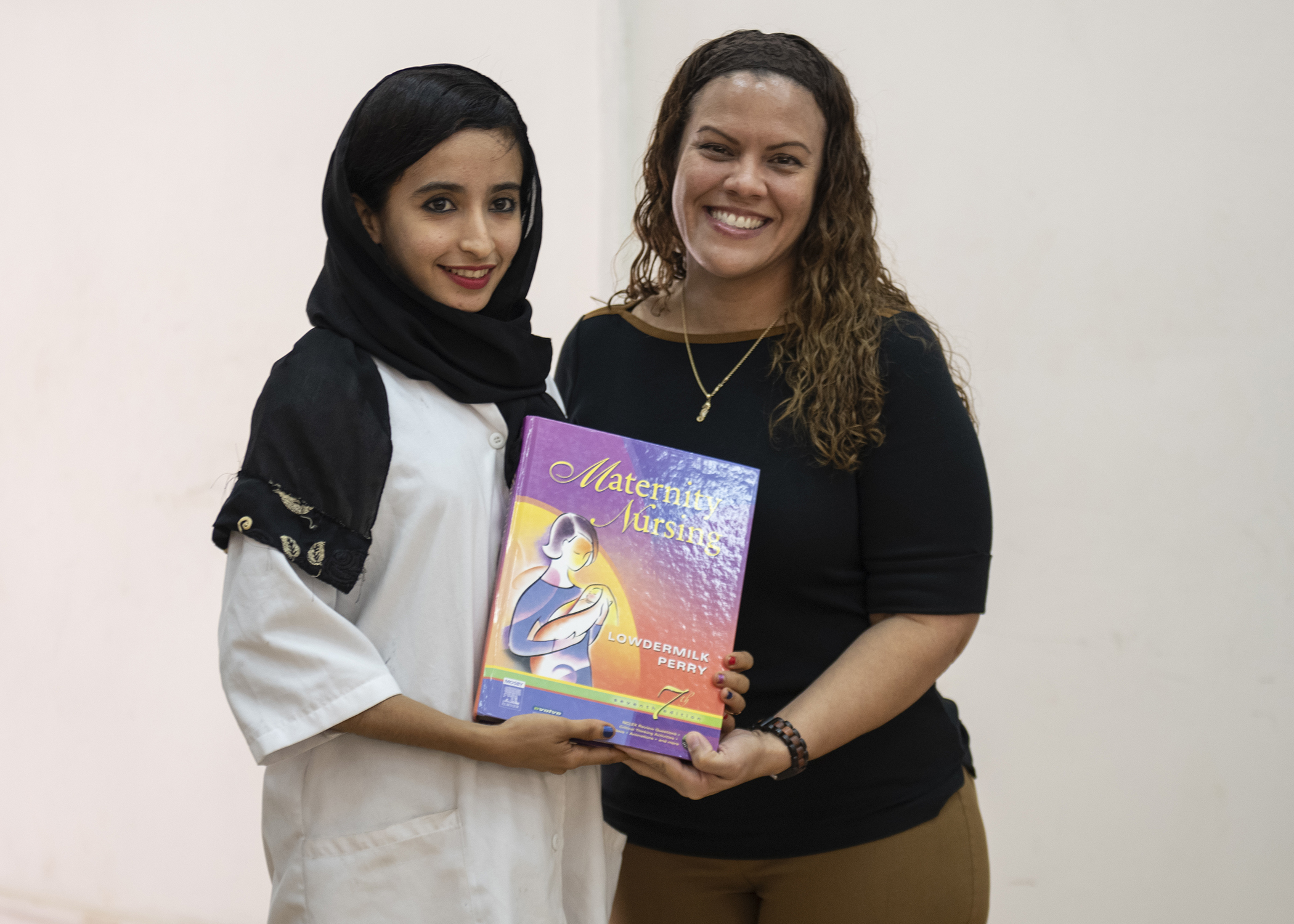 U.S. Army Maj. Ivette Blanco-Padilla, dental officer in charge, 403rd Civil Affairs Battalion (CAB), Combined Joint Task Force-Horn of Africa, Djibouti, gives a medical book to a student during a ceremony at the Djibouti Nursing School, Dec. 10, 2018. More than 30 students completed a semester-long medical English discussion group, facilitated by the 403rd CAB, which serves as a language laboratory where students develop practical linguistic and rhetorical skills through relationship building and information exchange. (U.S. Air Force photo by Tech. Sgt. Shawn Nickel)