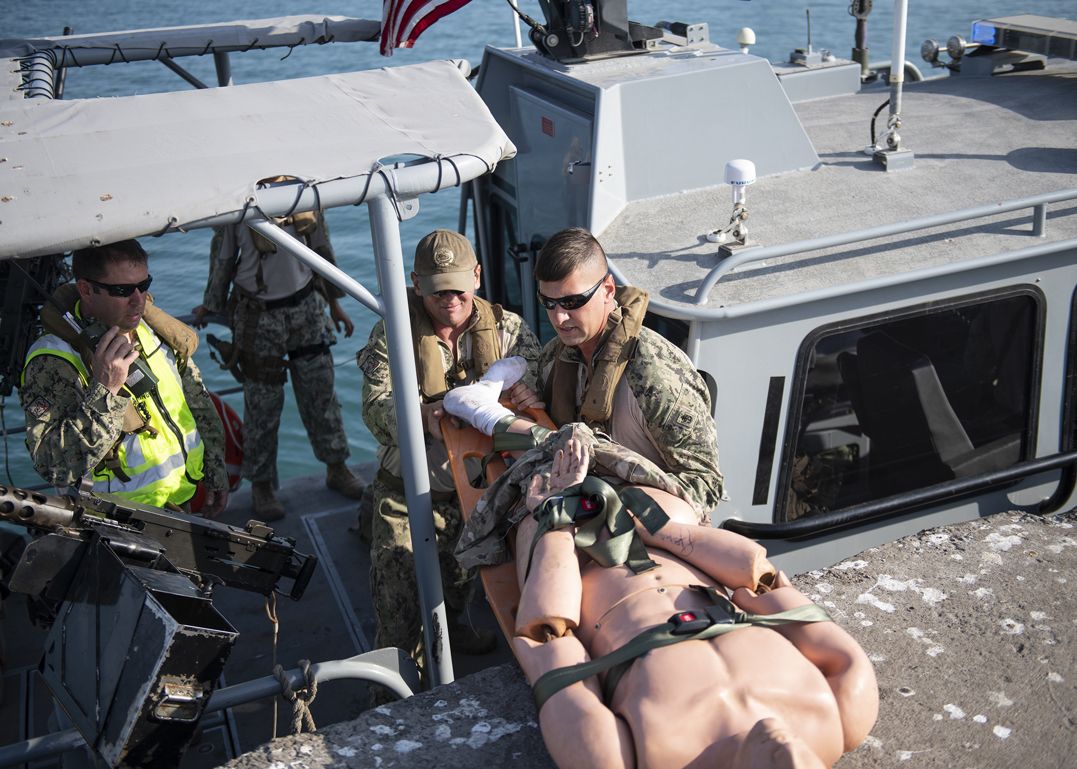 U.S. Navy Sailors from Coastal Riverine Squadron 8, Camp Lemonnier, Djibouti, transfer a simulated casualty off a Rigid Hull Inflatable Boat during the first-ever U.S. military exercise at the Port of Djibouti, Djibouti, Dec. 19, 2018. The exercise integrated U.S. Navy, Army and Djibouti Port Authority assets. (U.S. Air Force photo by Tech. Sgt. Shawn Nickel)