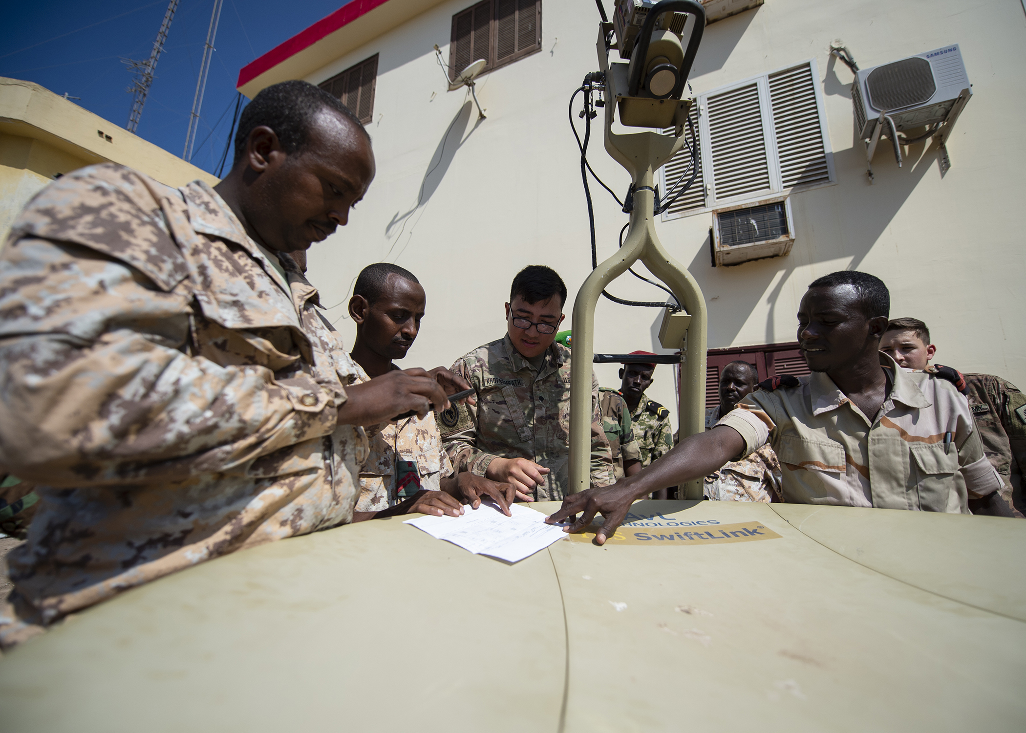 U.S. Army Spc. Legend Khotsombath, assigned to the Combined Joint Task Force-Horn of Africa communications directorate, explains parts of a satellite unit during an Africa Data Sharing Network (ADSN), version two, information exchange with Djibouti Army (FAD) soldiers at FAD Headquarters, Djibouti, Dec. 26, 2018. The ADSN works as an internal network that the African Union Mission in Somalia troop-contributing countries can use to communicate and share information amongst each other. (U.S. Air Force photo by Tech. Sgt. Shawn Nickel)