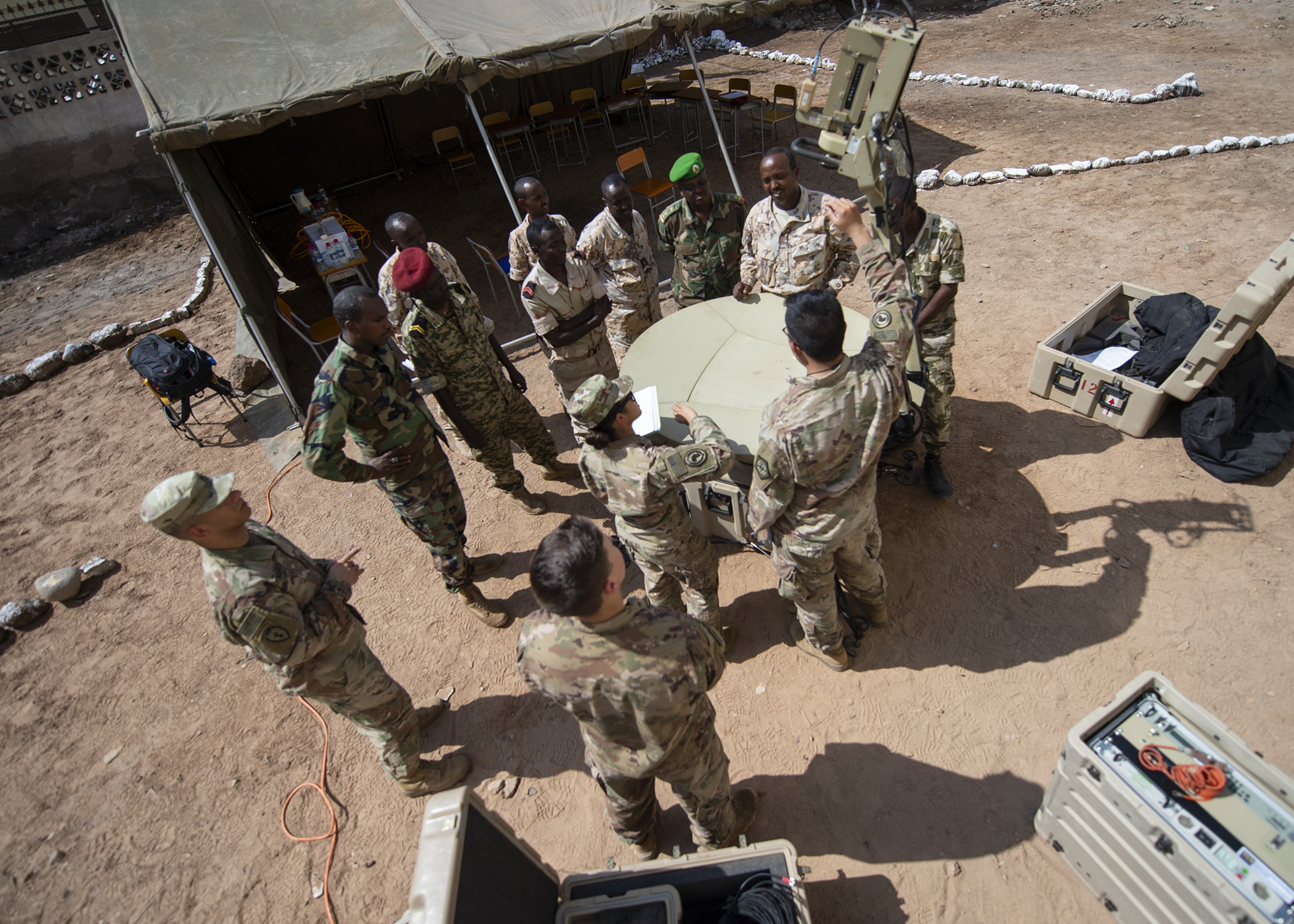 U.S. Army Spc. Christine Cantor, assigned to the Combined Joint Task Force-Horn of Africa communications directorate, explains safety while setting up a satellite unit during an Africa Data Sharing Network (ADSN), version two, information exchange with Djibouti Army (FAD) soldiers at FAD Headquarters, Djibouti, Dec. 26, 2018. The ADSN works as an internal network that the African Union Mission in Somalia troop-contributing countries can use to communicate and share information amongst each other. (U.S. Air Force photo by Tech. Sgt. Shawn Nickel)