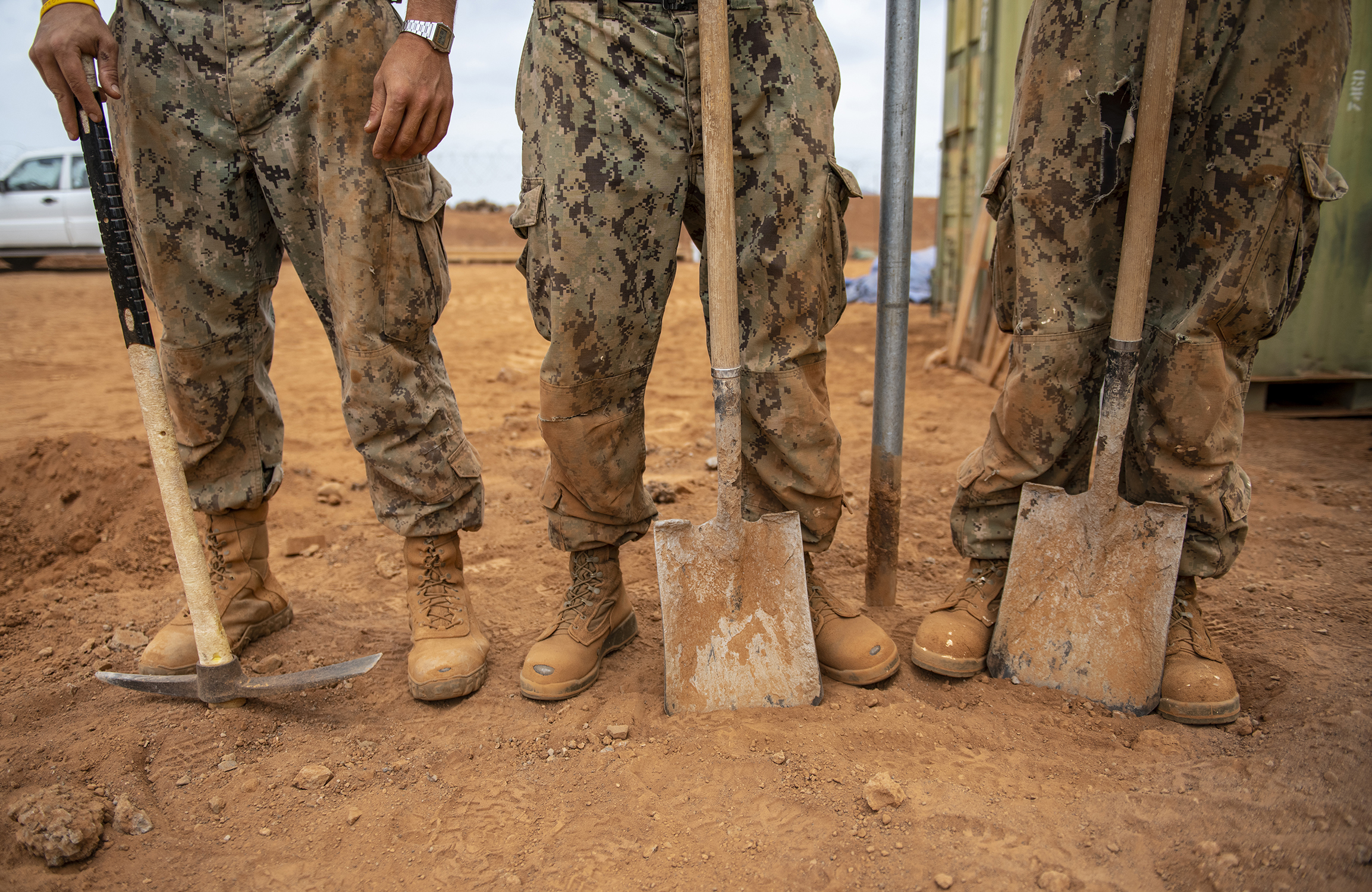 U.S. Navy Seabees assigned to Naval Mobile Construction Battalion 1, Combined Joint Task Force-Horn of Africa, Camp Lemonnier, Djibouti, wait for a piece of heavy equipment while building a fence during the construction of the future Ali Oune, Djibouti, Women's Medical Clinic, Dec. 27, 2018. The clinic is intended to enhance the Ministry of Health for Djibouti's ability to provide basic medical, birth and after care to the Ali Oune village and its more than 1,000 residents and rural neighbors. (U.S. Air Force photo by Tech. Sgt. Shawn Nickel)