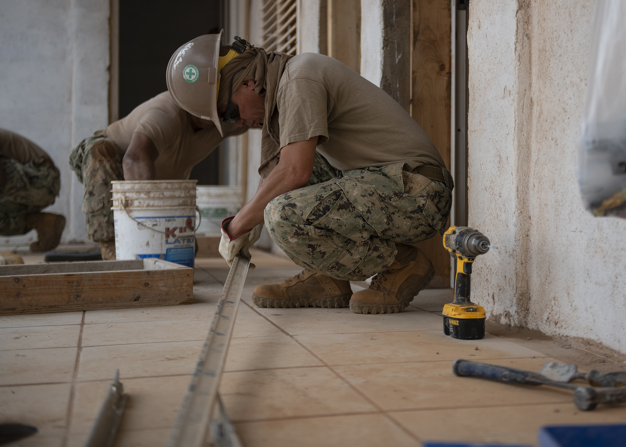 A U.S. Navy Seabee assigned to Naval Mobile Construction Battalion 1, Combined Joint Task Force-Horn of Africa, Camp Lemonnier, Djibouti, works on a drop ceiling during the construction of the future Ali Oune, Djibouti, Women's Medical Clinic, Dec. 27, 2018. The clinic is intended to enhance the Ministry of Health for Djibouti's ability to provide basic medical, birth and after care to the Ali Oune village and its more than 1,000 residents and rural neighbors. (U.S. Air Force photo by Tech. Sgt. Shawn Nickel)
