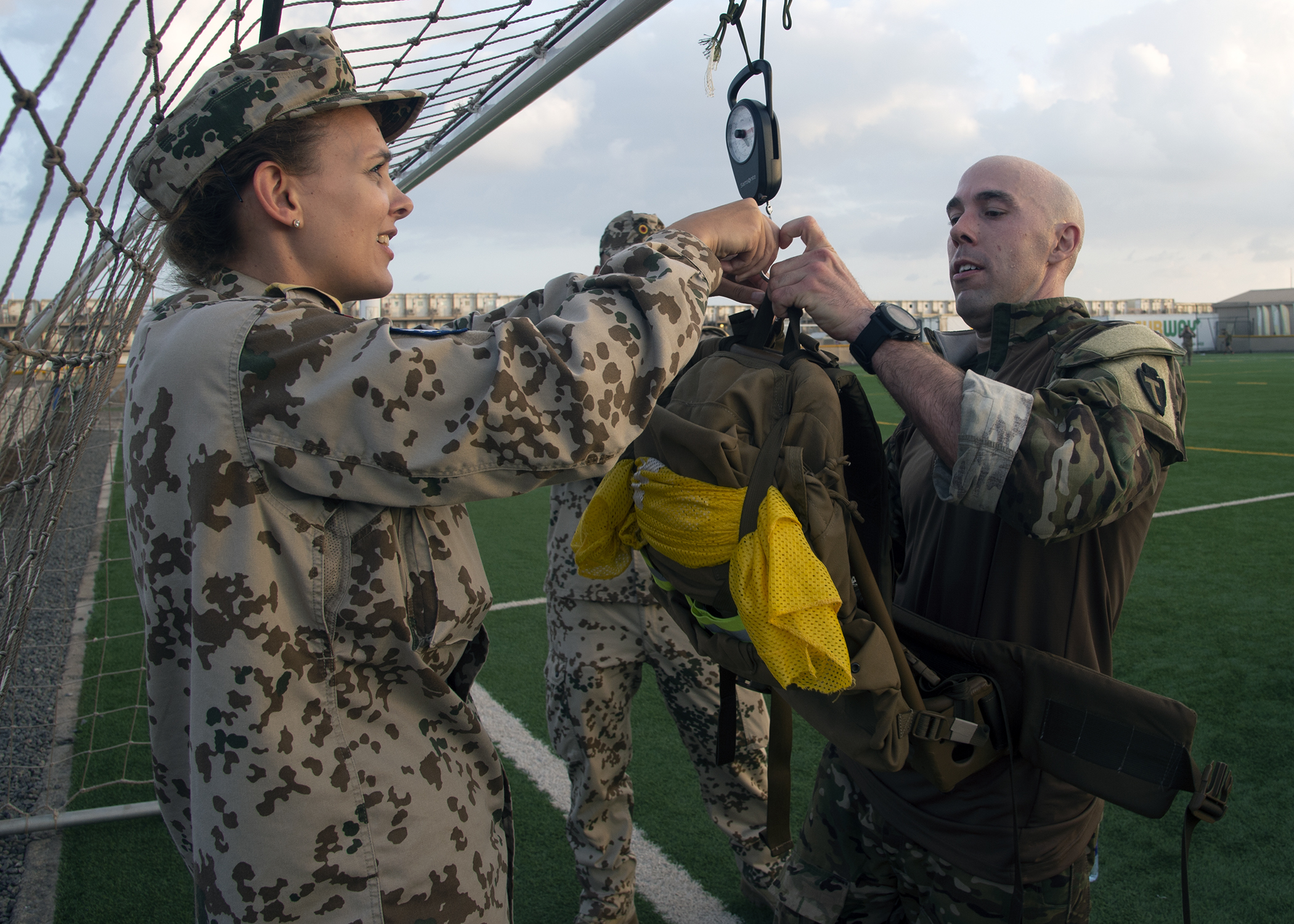 "U.S. Army Capt. Joseph Brunone, right, Headquarters and Headquarters Company, 1st Battalion, Task Force Alamo, Texas National Guard, assigned to Combined Joint Task Force-Horn of Africa (CJTF-HOA), Djibouti, has his backpack weighed by German Navy Lt. Cmdr. Katharina Wrede, after a ""ruckrun"" for the German Armed Forces Badge (GAFB) for Military Proficiency in Djibouti, Jan. 15, 2019. The GAFB is awarded to and worn by German service members of all ranks. Allied service members may also be awarded the badge, subject to their nations' uniform regulations. During the ""ruckrun"", backpacks are required to weight at or more than 33 pounds. (U.S. Navy photo by Mass Communication Specialist 1st Class Nick Scott)"