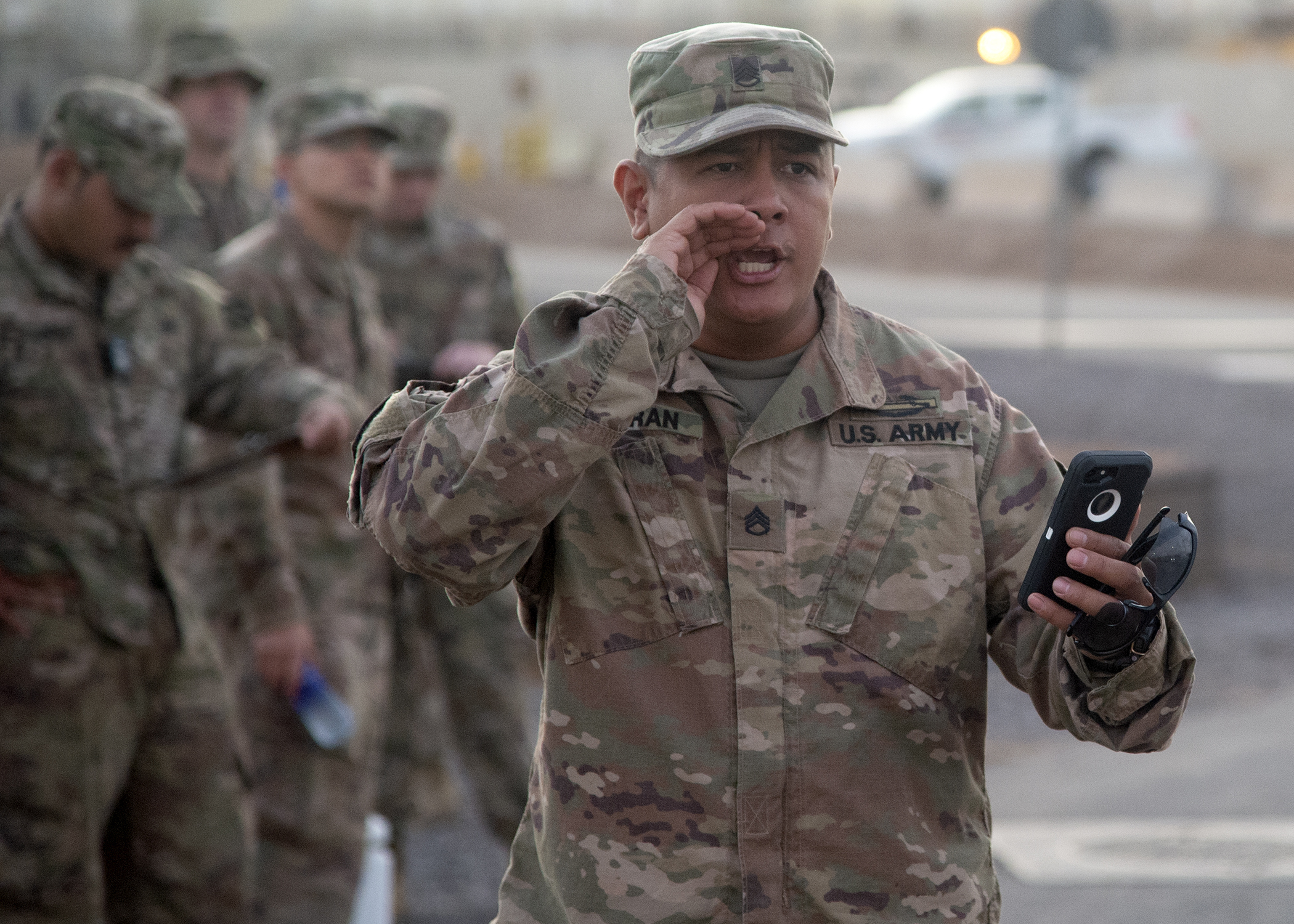 "U.S. Army Staff Sgt. Zachary Fejeran, Bowie Company, 1st Battalion, Task Force Alamo, Texas National Guard, assigned to Combined Joint Task Force-Horn of Africa (CJTF-HOA), Djibouti, calls out times during a ""ruckrun"" for the German Armed Forces Badge (GAFB) for Military Proficiency in Djibouti, Jan. 15, 2019. The GAFB is awarded to and worn by German service members of all ranks. Allied service members may also be awarded the badge, subject to their nations' uniform regulations. (U.S. Navy photo by Mass Communication Specialist 1st Class Nick Scott)"