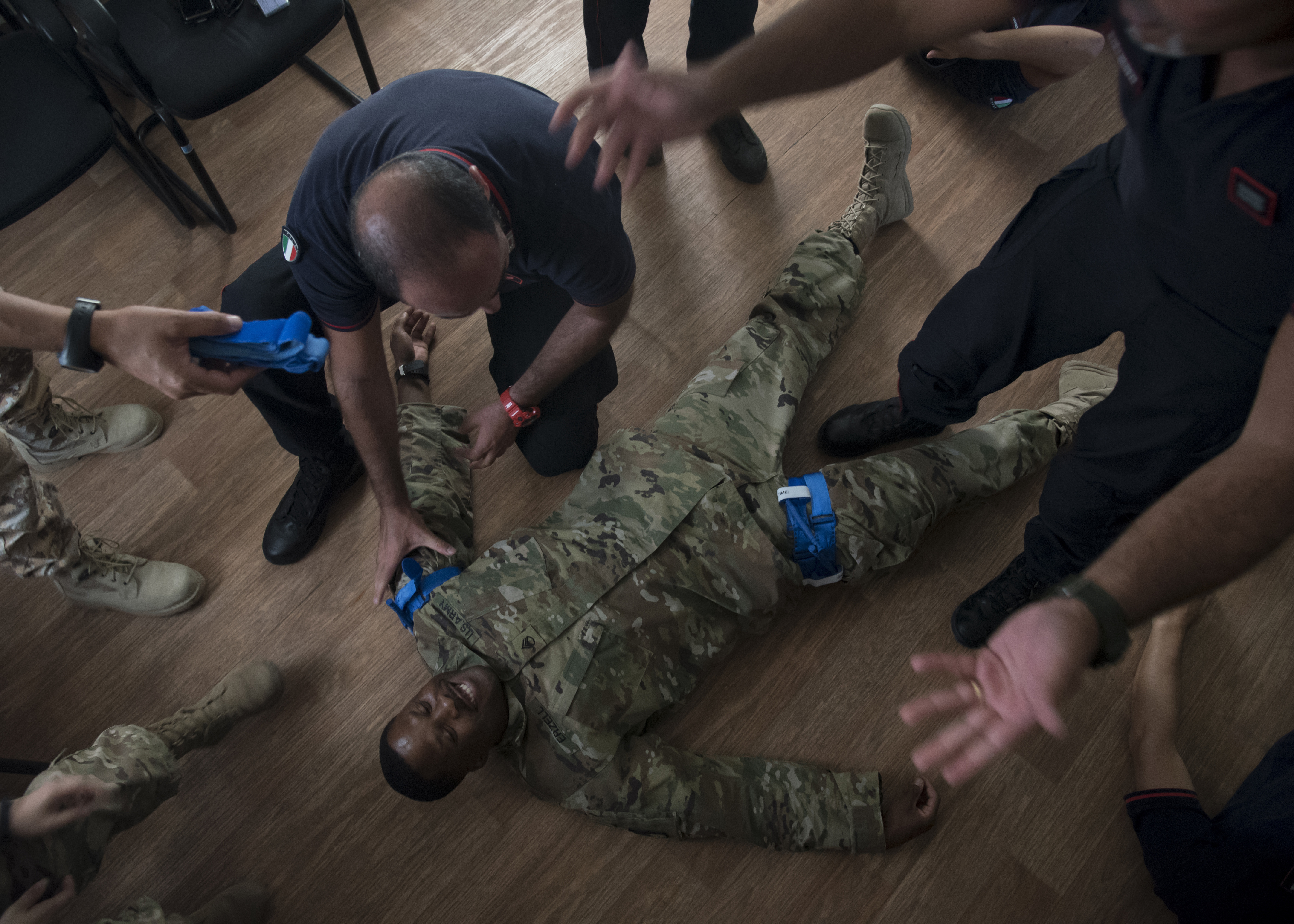 U.S. Army Staff Sgt. Duan Erzell, a communication's specialist with the 403rd Civil Affairs (CA) Battalion, participates in a tourniquet application demonstration as a simulated casualty during a Combat Lifesaver Course (CLS) at Base Militar Italiano de Supporte, Djibouti, Jan. 15, 2019. Proper tourniquet application is a primary focus of the CLS, a course medics from the 403rd CA Functional Specialty Team recently conducted for members of Base Militar Italiano de Supporte. (U.S. Air Force photo by Senior Airman Kirsten Brandes)