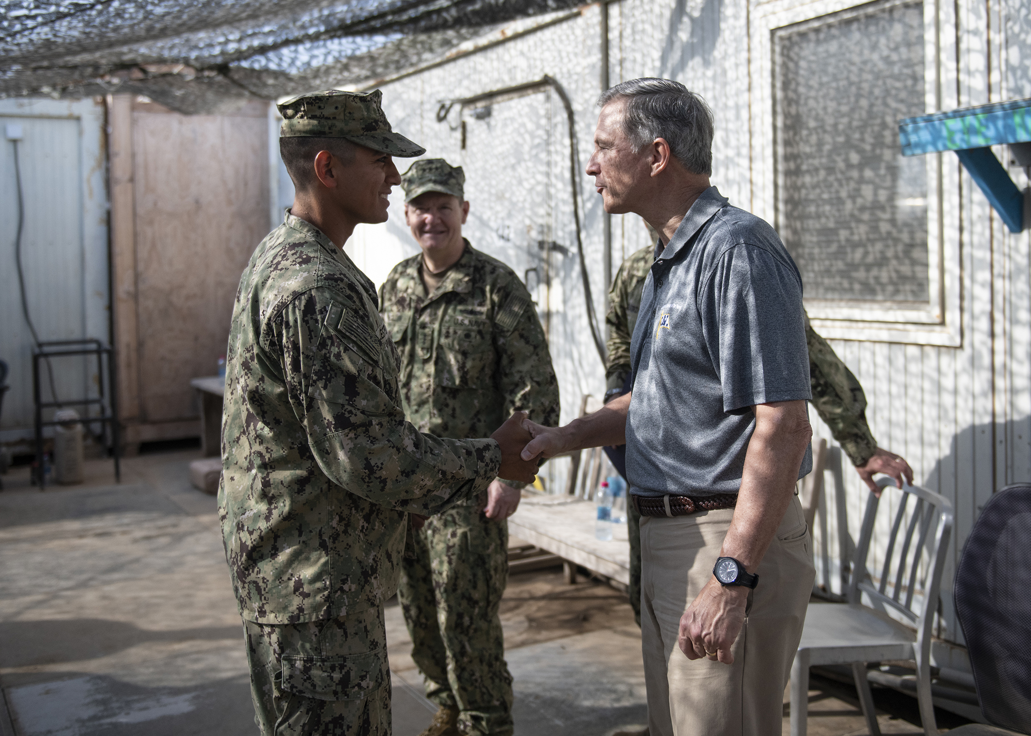 Assistant Secretary of the Navy (Manpower and Reserve Affairs), retired U.S. Navy Rear Adm. Gregory J. Slavonic presents a coin to U.S. Navy Petty Officer 2nd Class Jonathan Lester, from Naval Mobile Construction Battalion 1, assigned to Combined Joint Task Force - Horn of Africa, while visiting Camp Lemonnier, Djibouti, Feb. 3, 2019. Slavonic visited as part of a tour of Reserve units to answer questions, discuss leadership initiatives and interact with local Sailors. (U.S. Air Force photo by Tech. Sgt. Shawn Nickel)