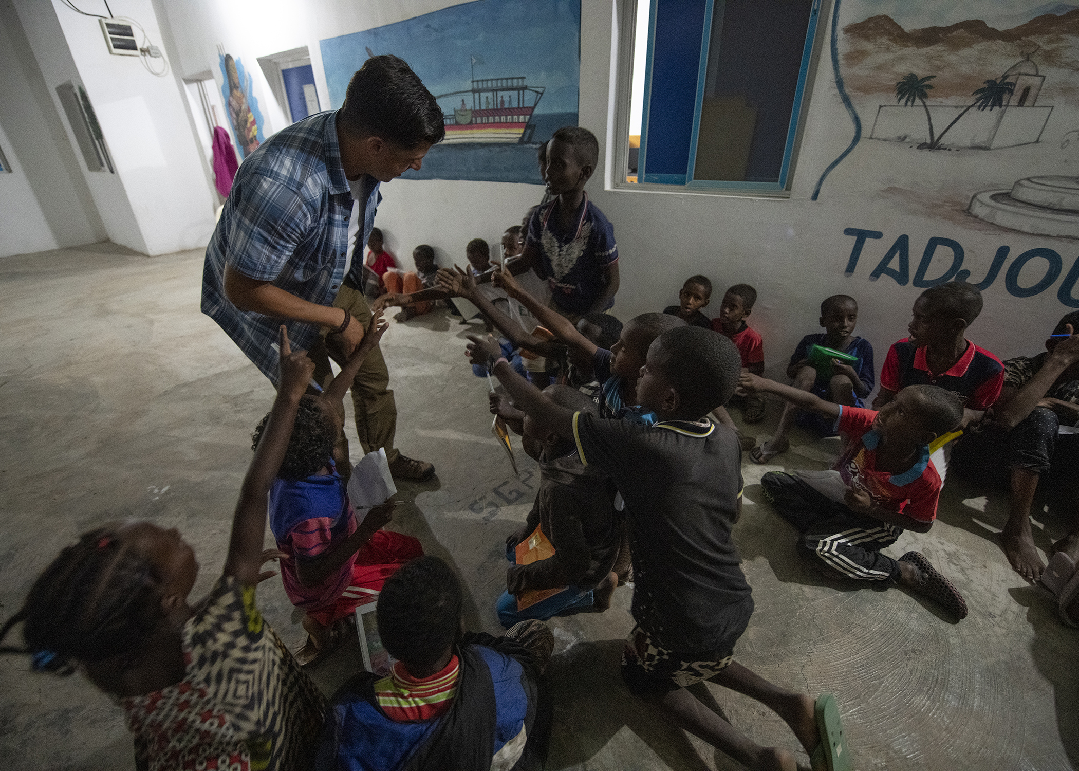 U.S. Army Staff Sgt. Brian Zimmerman, an operations NCO from the 403rd Civil Affairs Battalion, assigned to Combined Joint Task Force-Horn of Africa, works with children during an English Discussion Group in Tadjourah, Djibouti, Feb. 12, 2019. More than 90 Djiboutian youth and adults attended the group where students develop practical linguistic and rhetorical skills through conversation with English-speaking U.S. service members. (U.S. Air Force photo by Tech. Sgt. Shawn Nickel)