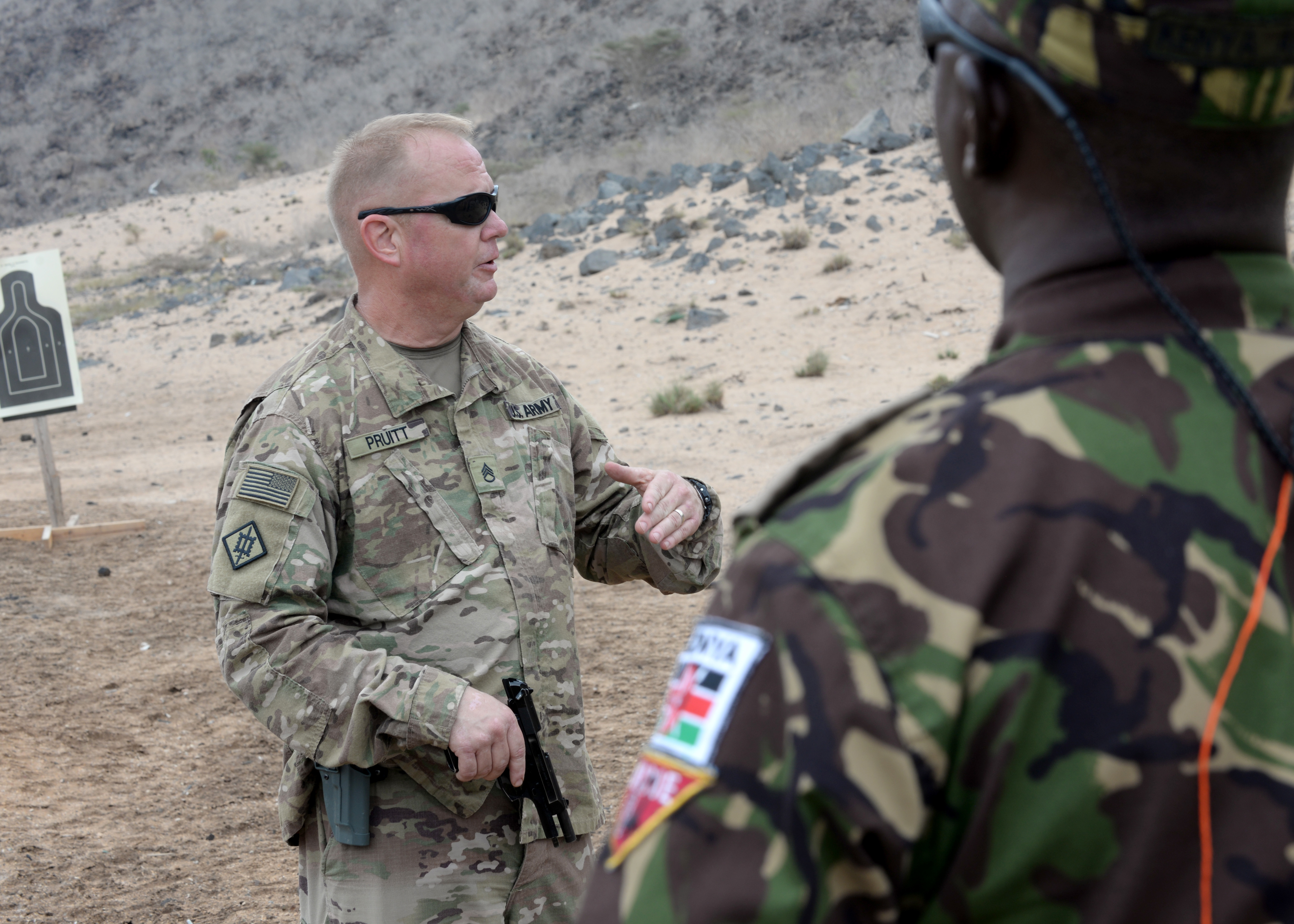 U.S. Army Staff Sgt. Kevin Pruitt, Headquarters Headquarters Company 1-141 Infantry Battalion, Task Force Alamo, Texas National Guard, fly away security team operations noncommissioned officer, deployed to Combined Joint Task Force-Horn of Africa (CJTF-HOA), briefs CJTF-HOA foreign liaison officers, about the Beretta M9 pistol during weapons familiarization at the Djibouti Range Complex, Arta, Djibouti, Feb. 16, 2019. The course gave the foreign liaison officers an insight on the Beretta M9 pistol and stance techniques used by U.S. military members. (U.S. Air Force photo by Staff Sgt. Franklin R. Ramos)