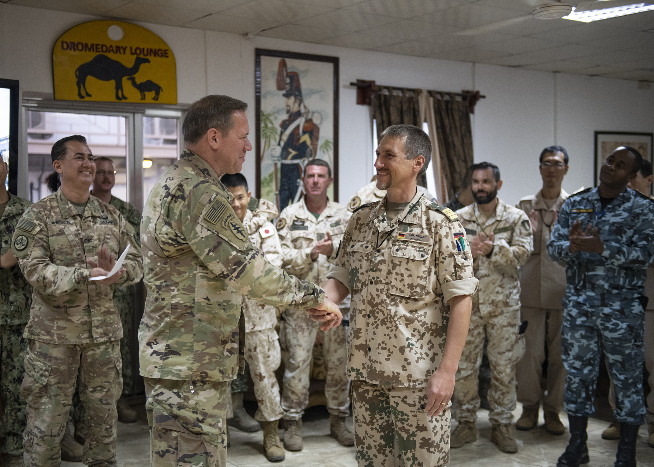U.S. Army Maj. Gen. James D. Craig, left, commanding general, Combined Joint Task Force-Horn of Africa, presents a coin to German Navy Cmdr. Dirk Muller, German detachment commander for the European Union Naval Force ATALANTA, the   European Union's integrated approach to combat piracy and armed robbery at sea off the Horn of Africa, during a cultural exchange event at Camp Lemonnier, Djibouti, Feb. 27, 2019. Multinational military partners affiliated with Camp Lemonnier hold monthly exchange events to strengthen alliances and attract new partners in the combined joint military environment. (U.S. Air Force photo by Tech. Sgt. Shawn Nickel)