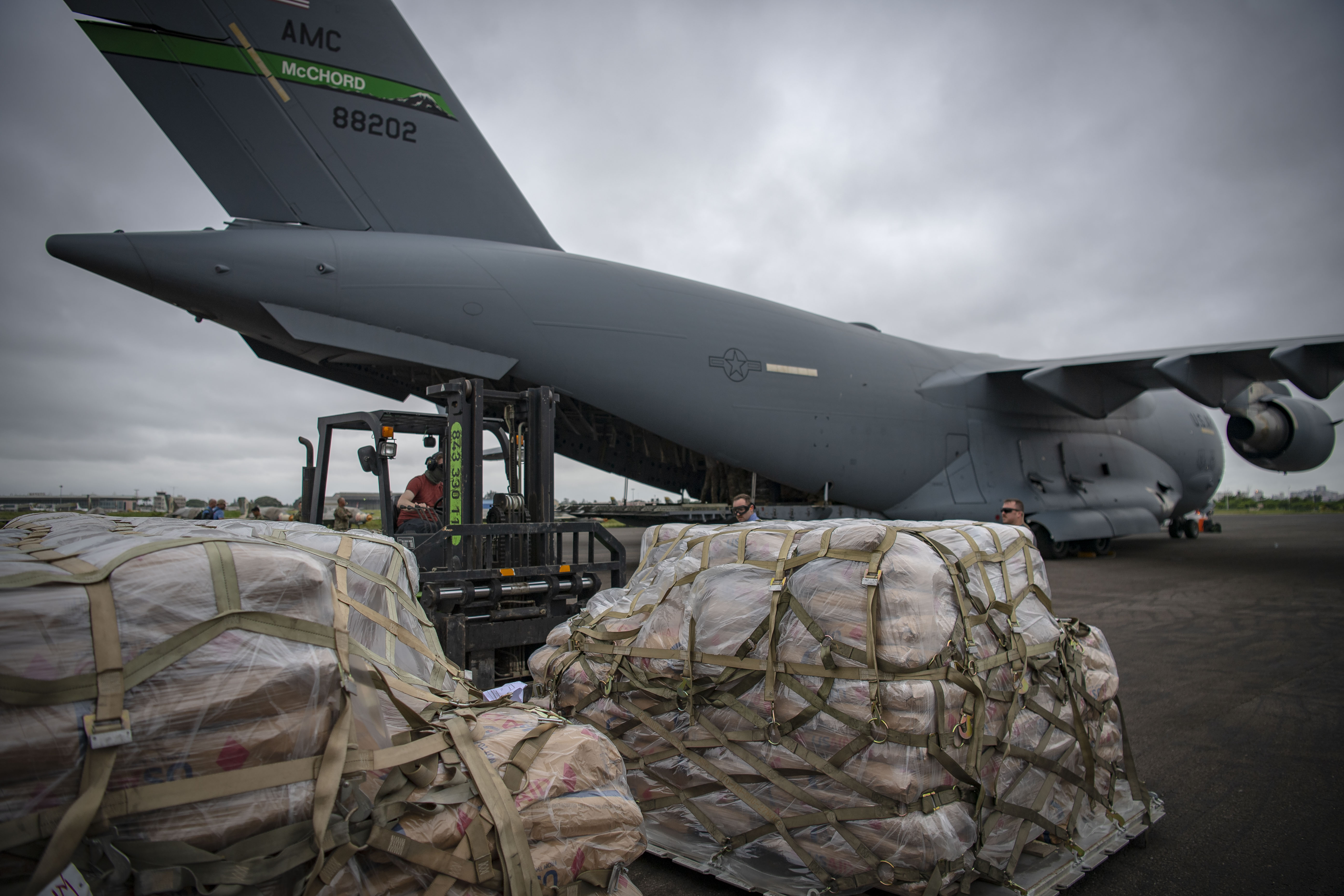 A U.S. Soldier loads bags of food on a C-130J Hercules assigned to the 75th Expeditionary Airlift Squadron, Combined Joint Task Force-Horn of Africa, at the airport in Maputo, Mozambique, March 29, 2019. The task force is helping meet requirements identified by USAID assessment teams and humanitarian organizations working in the region by providing logistics support and manpower to USAID at the request of the Government of the Republic of Mozambique. (U.S. Air Force Photo by Tech. Sgt. Chris Hibben)