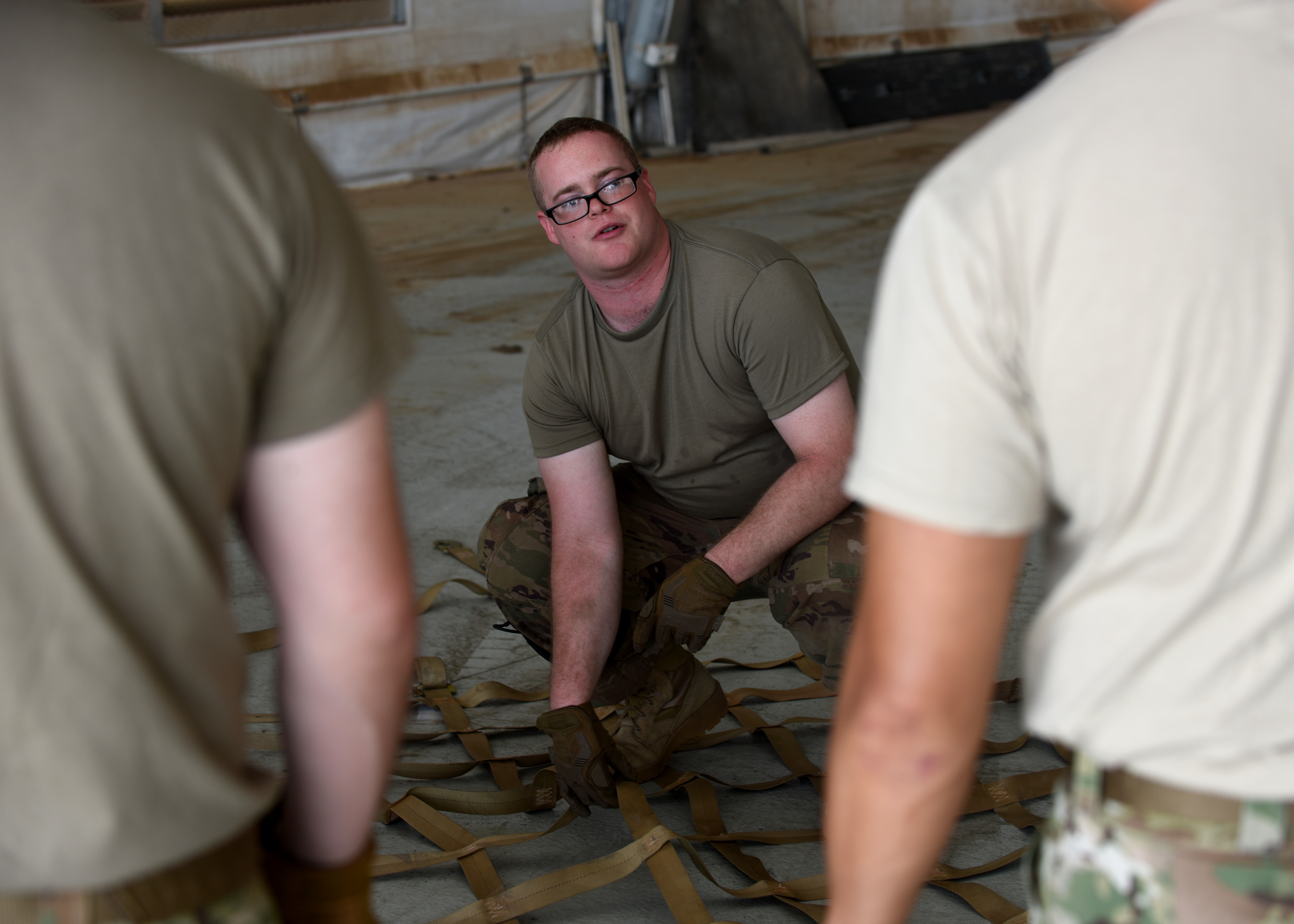 U.S. Air Force Senior Airman Cody Forth, mobile aerial porter for the 435th Contingency Response Group, Ramstein Air Base, Germany, supporting Combined Joint Task Force-Horn of Africa (CJTF-HOA), provides instructions for inspecting cargo nets used to transport U.S. Agency for International Development (USAID) supplies at Camp Lemonnier, Djibouti, April 1, 2019, for the U.S. Department of Defense's (DoD) relief effort in the Republic of Mozambique and surrounding areas following Cyclone Idai. Teams supporting CJTF-HOA, which is leading the DoD relief effort, prepared cargo for transport following a call for assistance from the USAID Disaster Assistance Response Team. (U.S. Air Force photo by Staff Sgt. Franklin R. Ramos)
