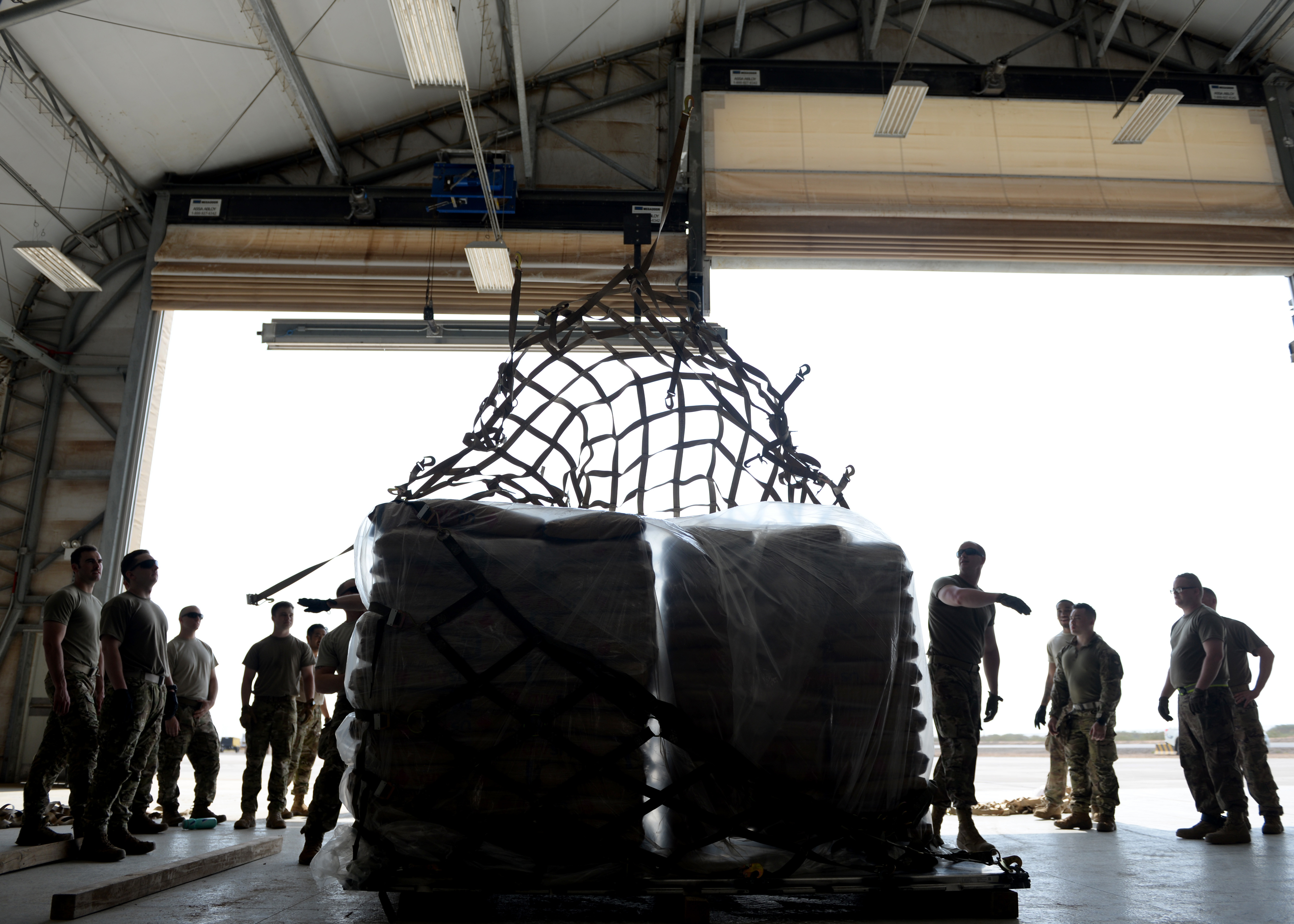 U.S. Air Force Airmen from the 435th Contingency Response Group, Ramstein Air Base, Germany, currently at Camp Lemonnier, Djibouti, supporting Combined Joint Task Force-Horn of Africa (CJTF-HOA), prepare a cargo pallet used to transport U.S. Agency for International Development (USAID) supplies at Camp Lemonnier, April 1, 2019, for the U.S. Department of Defense's (DoD) humanitarian relief effort in the Republic of Mozambique and surrounding areas following Cyclone Idai. Teams supporting CJTF-HOA, which is leading the DoD relief effort, prepared cargo for transport following a call for assistance from the USAID Disaster Assistance Response Team. (U.S. Air Force photo by Staff Sgt. Franklin R. Ramos)