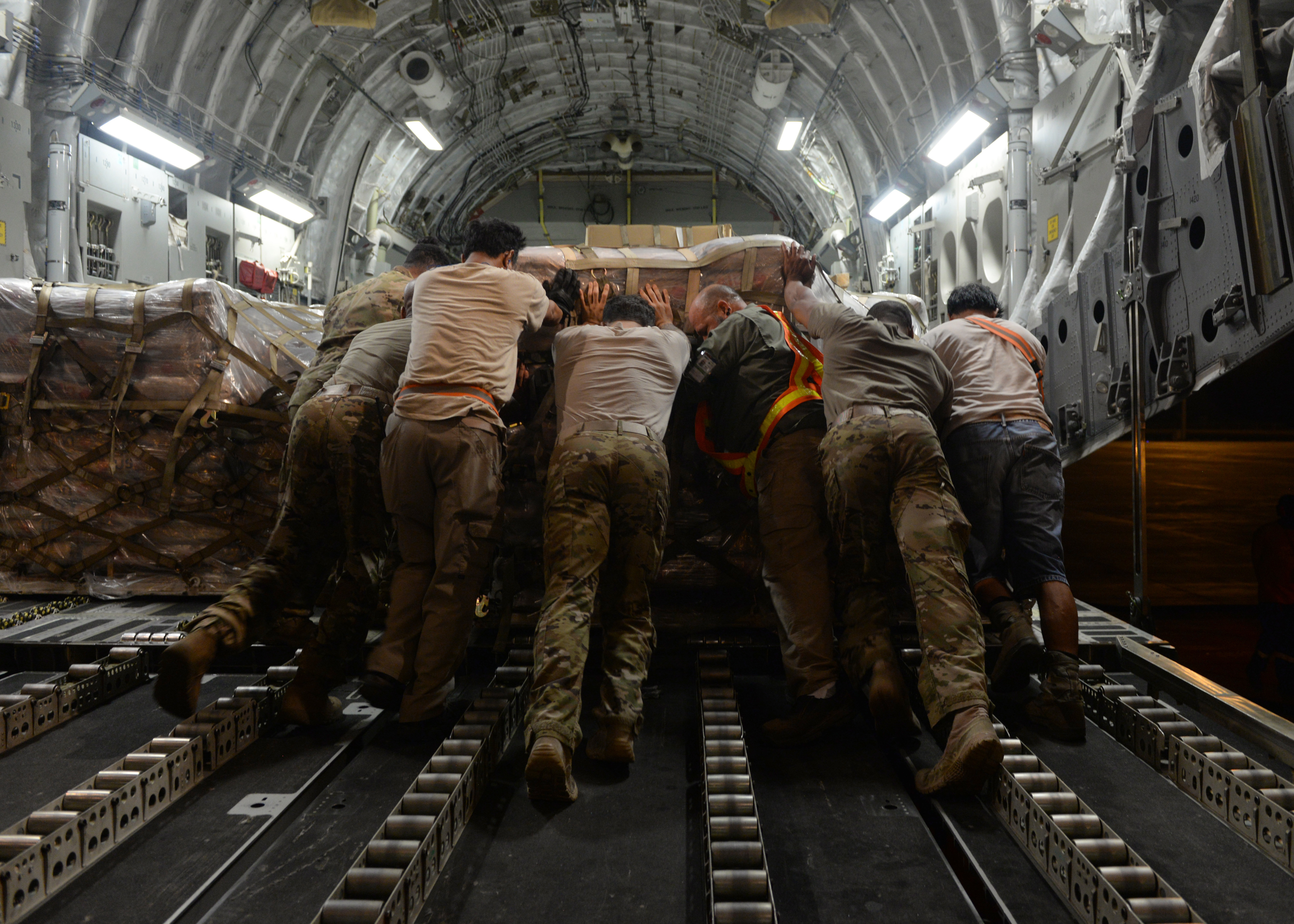 Department of Defense personnel load a U.S. Agency for International Development (USAID) food pallet onto a U.S. Air Force C-17 Globemaster III, assigned to Joint Base Lewis-McChord, Washington, supporting Combined Joint Task Force-Horn of Africa (CJTF-HOA), at Camp Lemonnier, Djibouti, April 2, 2019, for the U.S. Department of Defense's (DoD) humanitarian relief effort in the Republic of Mozambique and surrounding areas following Cyclone Idai. CJTF-HOA, which is leading the DoD relief effort, transported 17,400 pounds of USAID food, a forklift, a 25K loader and palletizing equipment on the C-17 to Mozambique following a call for assistance from the USAID Disaster Assistance Response Team. (U.S. Air Force photo by Staff Sgt. Franklin R. Ramos)
