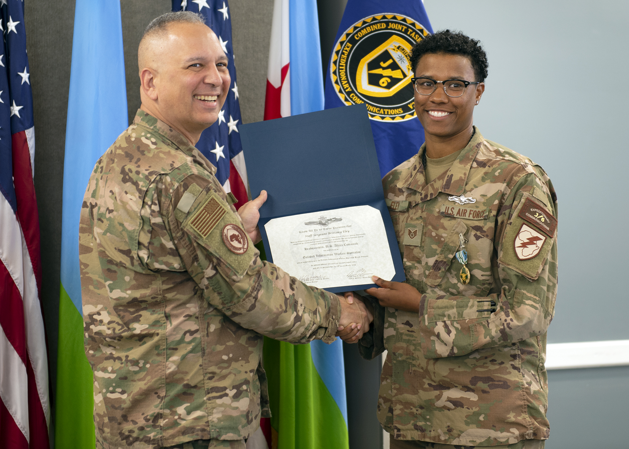 U.S. Air Force Col. Kjäll Gopaul, communications director for Combined Joint Task Force-Horn of Africa (CJTF-HOA), presents a U.S. Navy enlisted information warfare specialist (EIWS) certificate to U.S. Air Force Staff Sgt. Brittany Eley, Joint Network Control Center team lead assigned to CJTF-HOA, at Camp Lemonnier, Djibouti, April 1, 2019. Eley has been recognized as the first sister-service EIWS in CJTF-HOA, which signifies that an eligible Sailor has achieved a level of excellence and proficiency in their rating. (U.S. Air Force photo by Master Sgt. Amanda Currier)