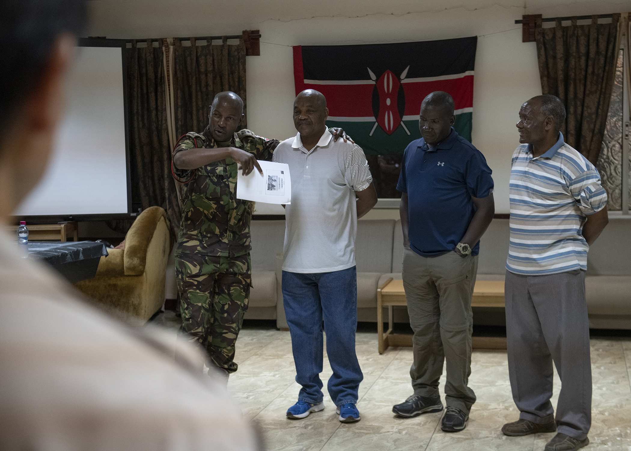 Kenya Defence Force Lt. Col. Victor Mburu, a foreign liaison officer assigned to Combined Joint Task Force-Horn of Africa (CJTF-HOA), introduces fellow countrymen who work on Camp Lemonnier, Djibouti, to multinational military partners while presenting information on his home country during a cultural exchange event at Camp Lemonnier, March 27, 2019. CJTF-HOA holds monthly exchange events with multinational military partners affiliated with Camp Lemonnier to strengthen alliances and attract new partners in the combined joint military environment. (U.S. Air Force photo by Tech. Sgt. Shawn Nickel)