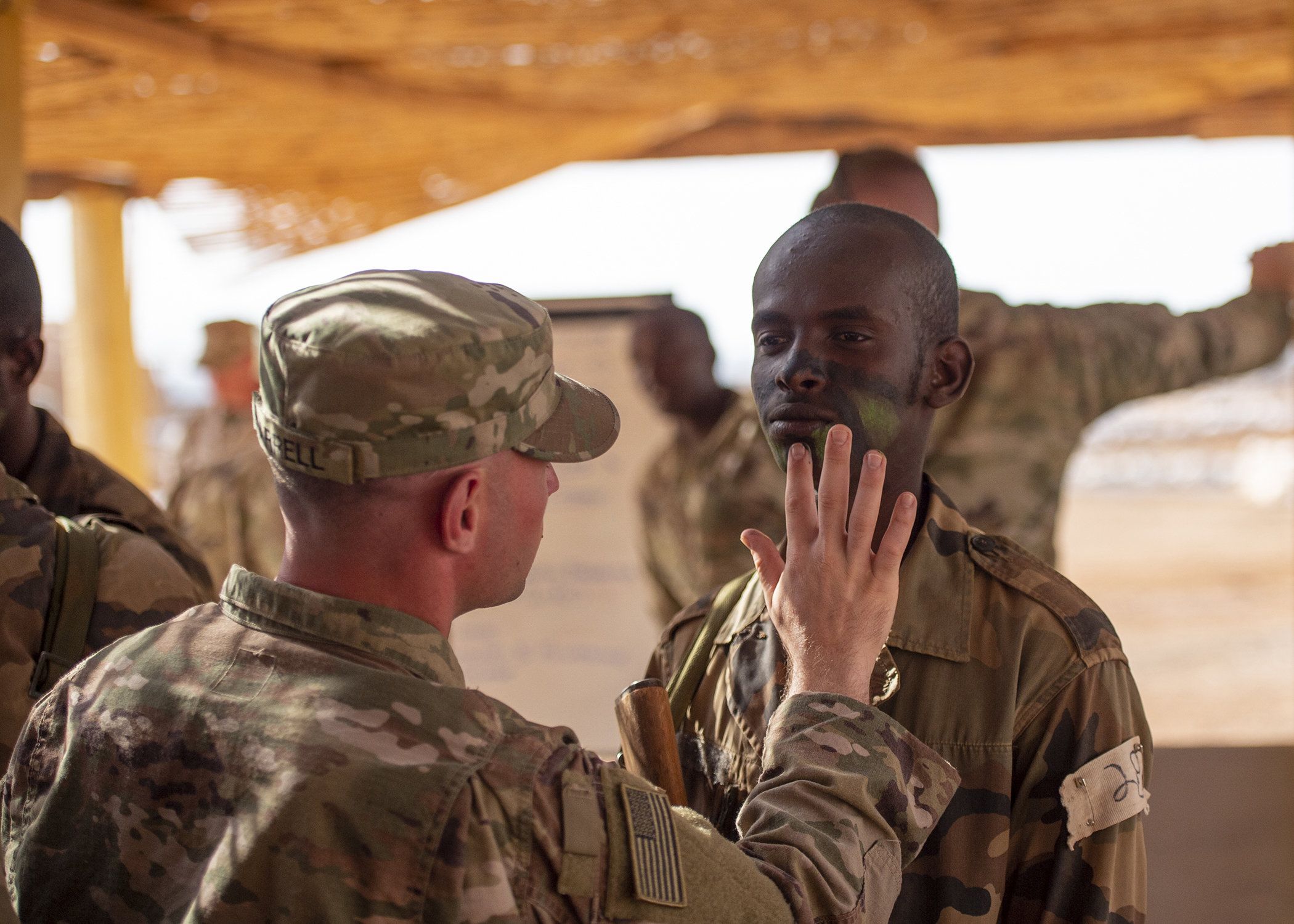 A U.S. Army Soldier with Headquarters Company, 1-26 Infantry Battalion, 2nd Brigade Combat Team, 101st Airborne, assigned to Combined Joint Task Force-Horn of Africa, helps a soldier from the Rapid Intervention Battalion (RIB), the Djiboutian army's elite military force, prepare for a visit from U.S. Marine Corps Gen. Thomas D. Waldhauser, commander of U.S. Africa Command, and Chief of General Staff of the Djibouti Armed Forces Zakaria Cheik Ibrahim, at a training base in Djibouti, March 21, 2019. Waldhauser and Zakaria visited in order to discuss the growth and development of Djiboutian security forces. (U.S. Air Force photo by Tech. Sgt. Shawn Nickel)