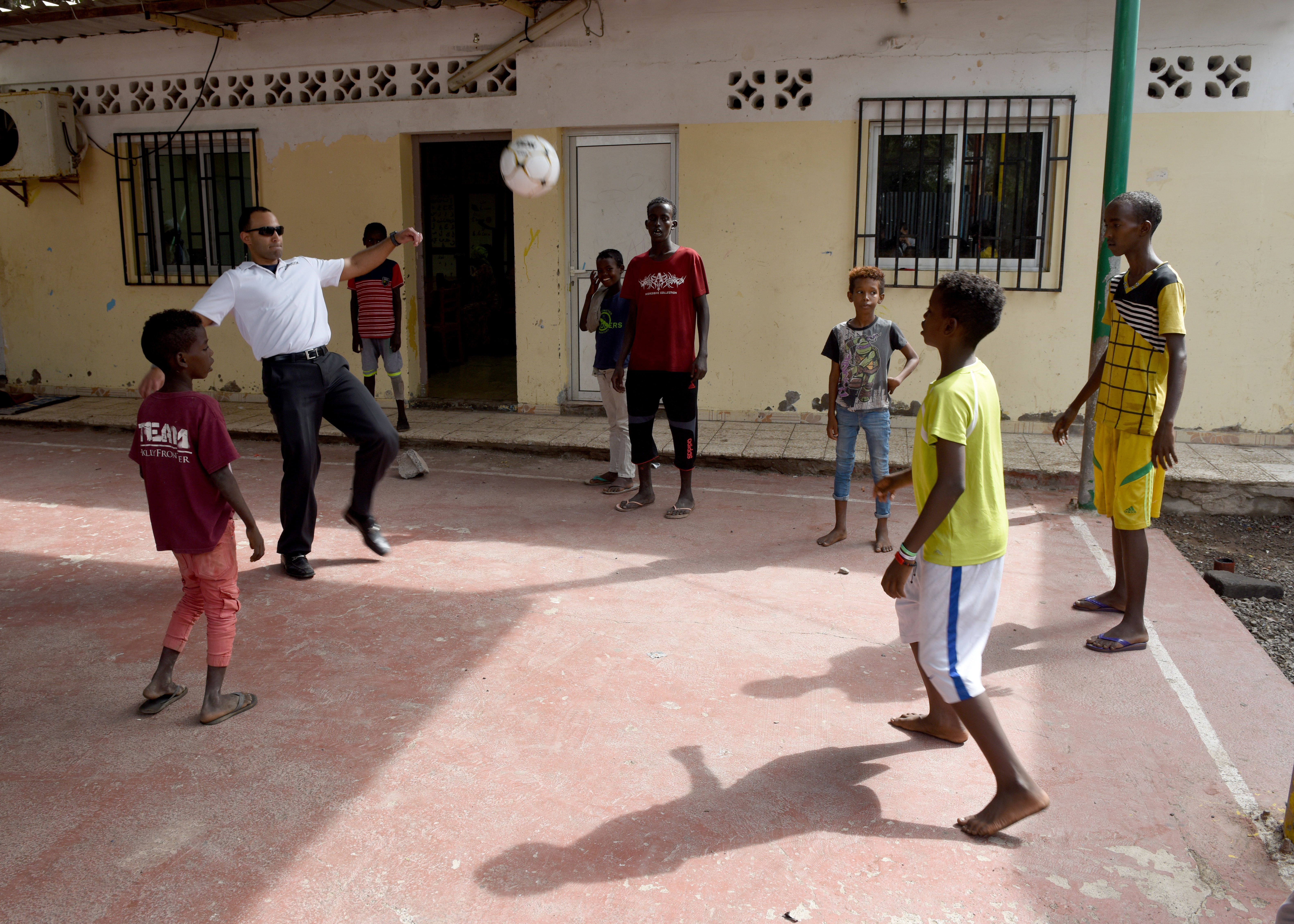 U.S. Army 1st Lt. Luis Alvarez, chaplain candidate with the Massachusetts National Guard, kicks a soccer ball with children at Caritas in Djibouti City, Djibouti, while visiting Combined Joint Task Force-Horn of Africa (CJTF-HOA), April 25, 2019. Caritas is a day center that provides care to nearly 100 children a day and enables CJTF-HOA members with a unique opportunity to interact with the local community through cultural exchanges in Djibouti City. (U.S. Air Force Photo by Staff Sgt. Franklin R. Ramos)