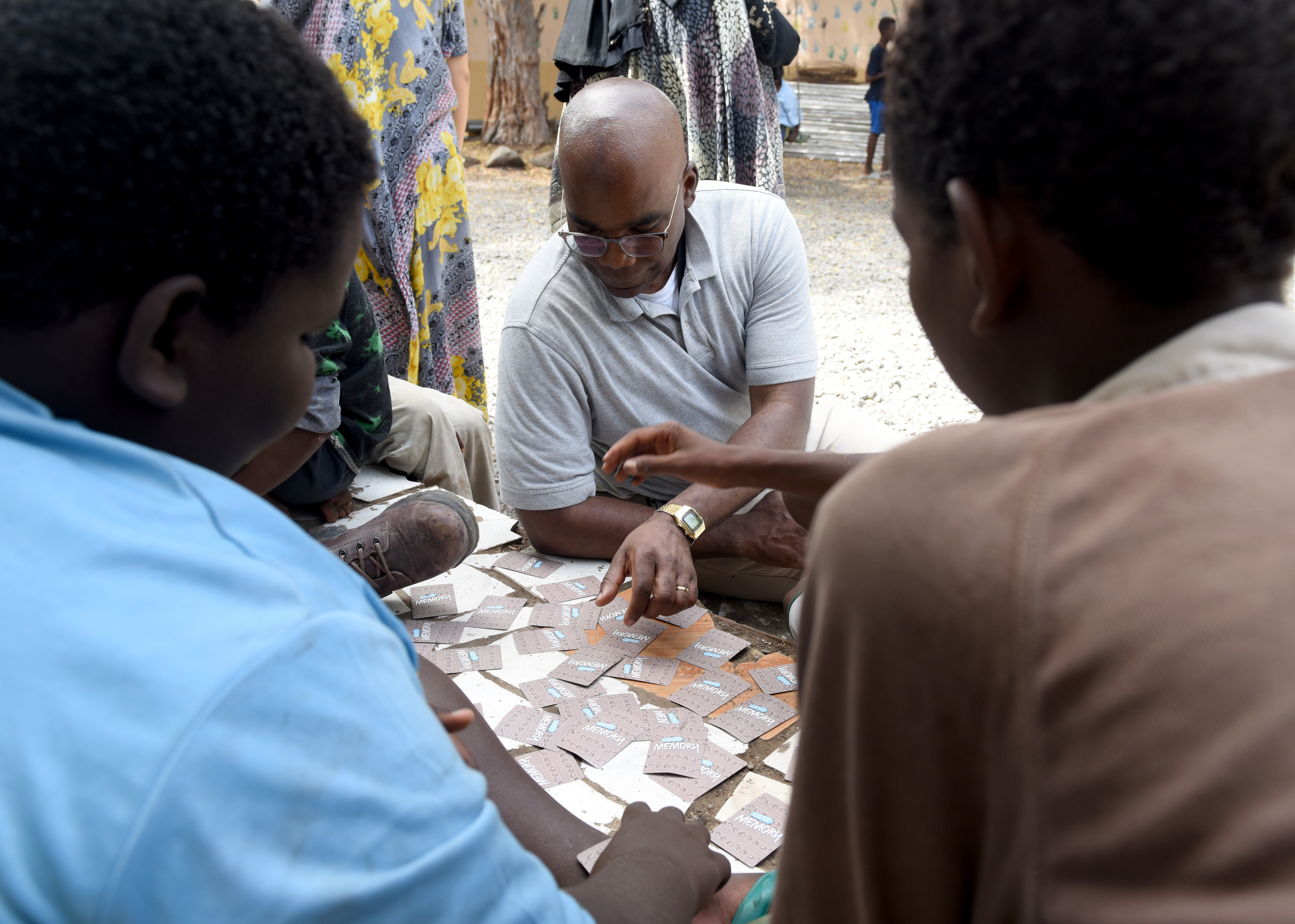 U.S. Army Col. Paul Minor, chaplain with the Massachusetts National Guard, plays a card matching game with children at Caritas in Djibouti City, Djibouti, while visiting Combined Joint Task Force-Horn of Africa (CJTF-HOA), April 25, 2019. CJTF-HOA enhances partner capabilities by providing bi-weekly assistance to Caritas, which is an international organization that was started in 1897 by the Catholic Church to provide relief to the world. (U.S. Air Force Photo by Staff Sgt. Franklin R. Ramos)