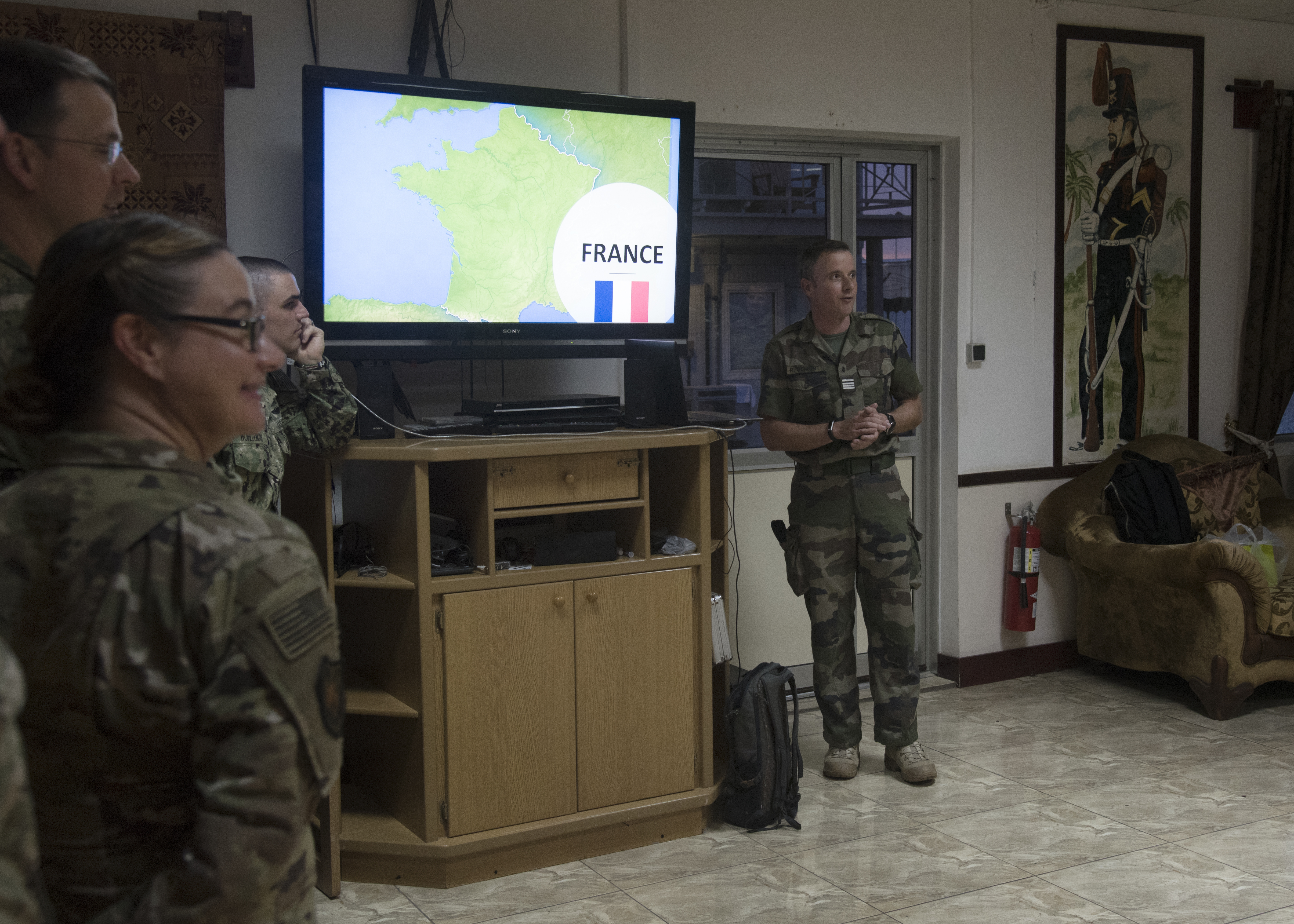 French army Maj. Romain, a foreign liaison officer assigned to Combined Joint Task Force-Horn of Africa (CJTF-HOA), briefs multinational military partners about his country during a CJTF-HOA cultural exchange at Camp Lemonnier, Djibouti, May 22, 2019. CJTF-HOA holds monthly exchanges with multinational military partners affiliated with Camp Lemonnier to strengthen alliances and increase understanding within the combined joint military environment. (U.S. Air Force photo by Staff Sgt. Kirsten Brandes)