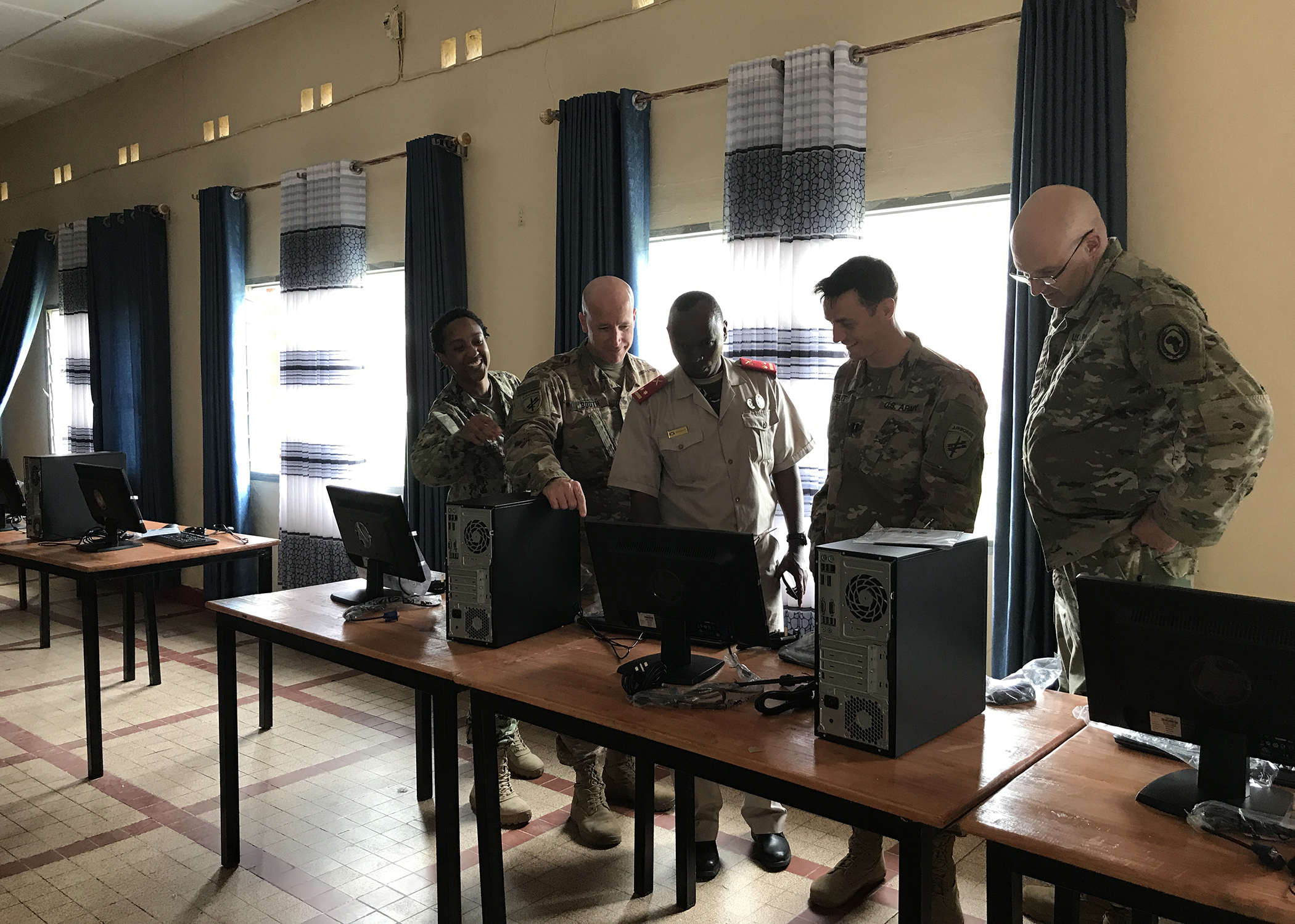 Combined Joint Task Force-Horn of Africa service members look at computer equipment, provided by Spirit of America, in the library of the Burundi National Defence Force Senior Command and Staff College (SCSC), in Kinanira, Burundi, May 15, 2019.  A team of CJTF-HOA service members visited Burundi to discuss best practices with the Burundi SCSC students. (Courtesy Photo)