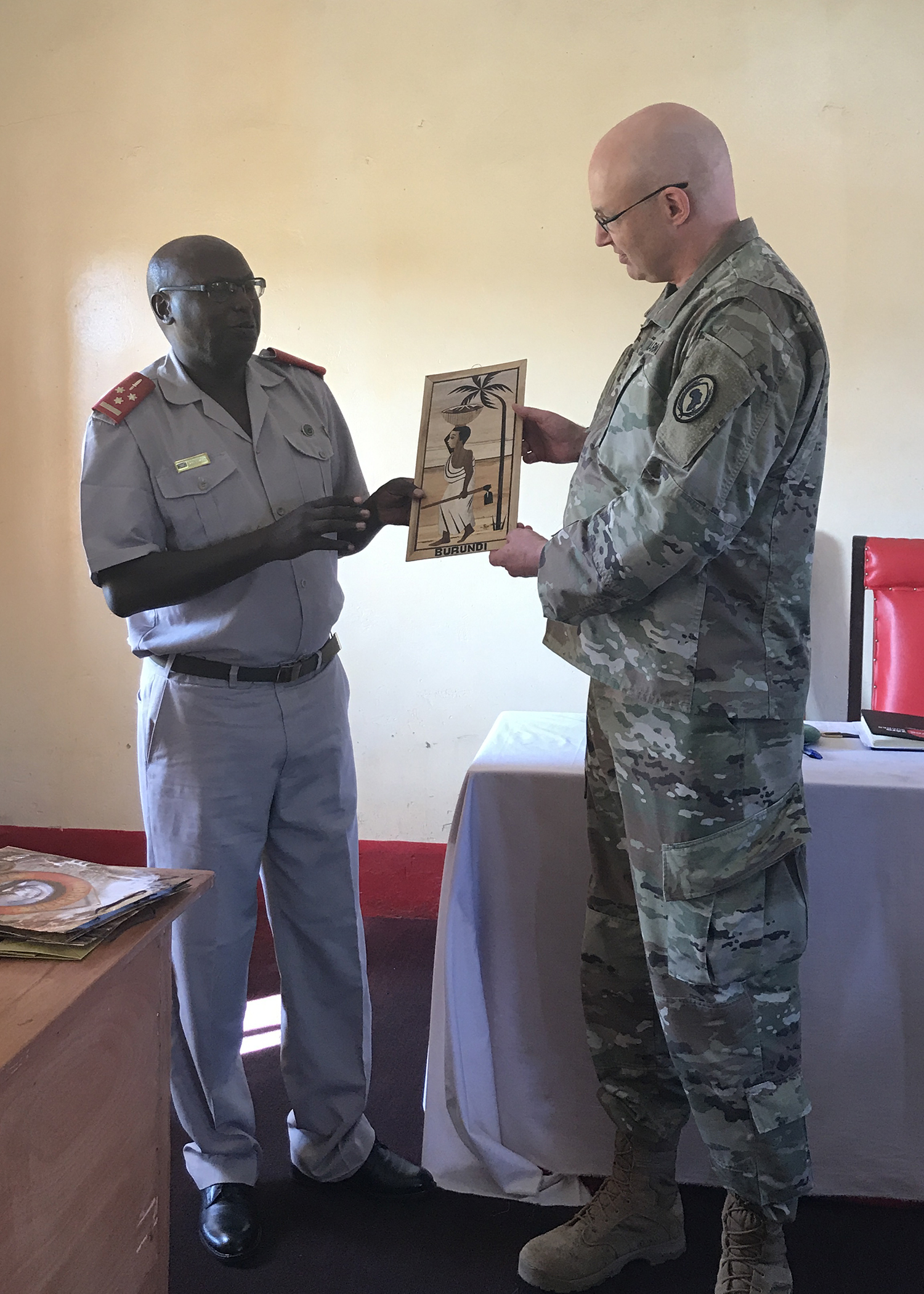 U.S. Army Lt. Col. Steve Gerber, a Maryland Army National Guard member mobilized as the Combined Joint Task Force-Horn of Africa information operations chief, participates in a gift exchange with Burundi National Defence Force Col. C Ntacebera, commandant of the Senior Command and Staff College (SCSC), in Kinanira, Burundi, May 17, 2019.  Gerber was part of a four-person team of CJTF-HOA service members who visited Burundi to discuss best practices with the Burundi SCSC students. (Courtesy Photo)