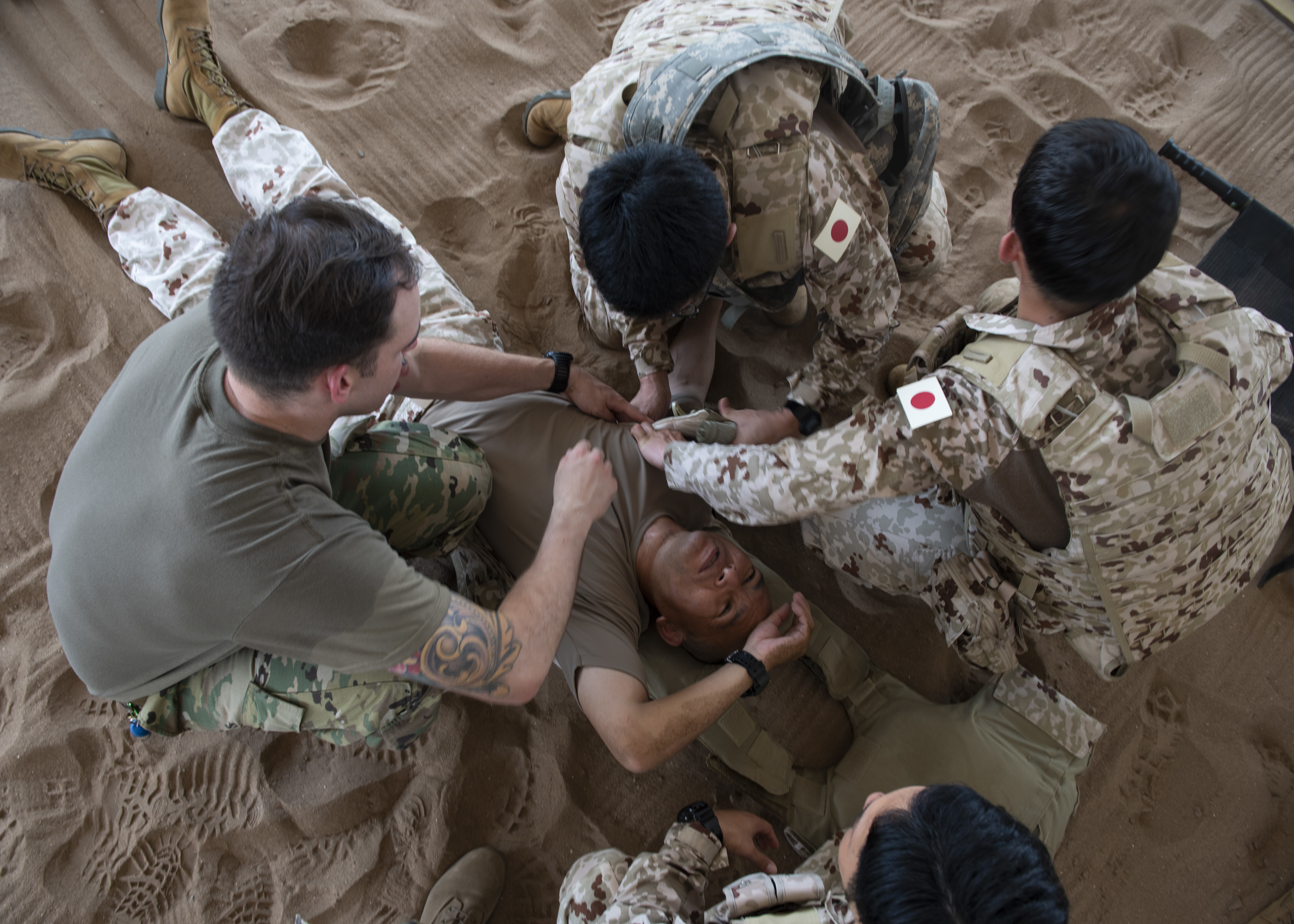 U.S. Army Sgt. Barrey Paddock, senior medic for Delta Company, 403rd Civil Affairs Battalion, assigned to Combined Joint Task Force-Horn of Africa, and Japanese Ground Self-Defense Force soldiers treat a victim during a tactical combat casualty care (TCCC) medical exchange at Camp Lemonnier, Djibouti, June 3, 2019. TCCC provided partner nation Soldiers an opportunity to share different methods on how to conduct life-saving medical care on a battlefield. (U.S. Air Force photo by Staff Sgt. Franklin R. Ramos)