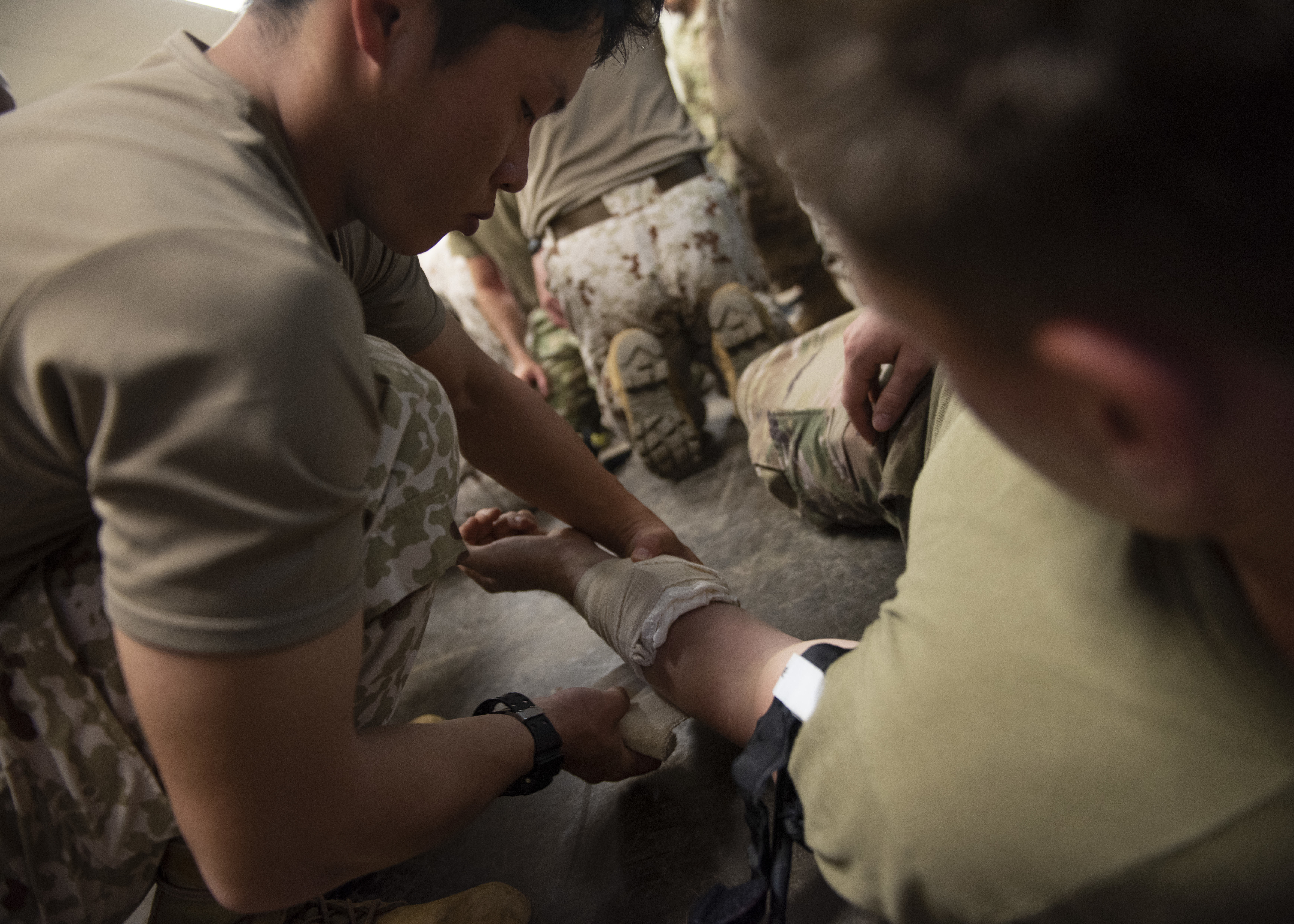 A Japanese Ground Self-Defense Force soldier applies a bandage to a U.S. Army Soldier, assigned to Combined Joint Task Force-Horn of Africa, during a tactical combat casualty care course at Camp Lemonnier, Djibouti, May 27, 2019. The course was part of a two-day subject matter expert medical exchange that focused on first-aid methodologies between the two partner nations in Djibouti. (U.S. Air Force photo by Staff Sgt. Franklin R. Ramos)