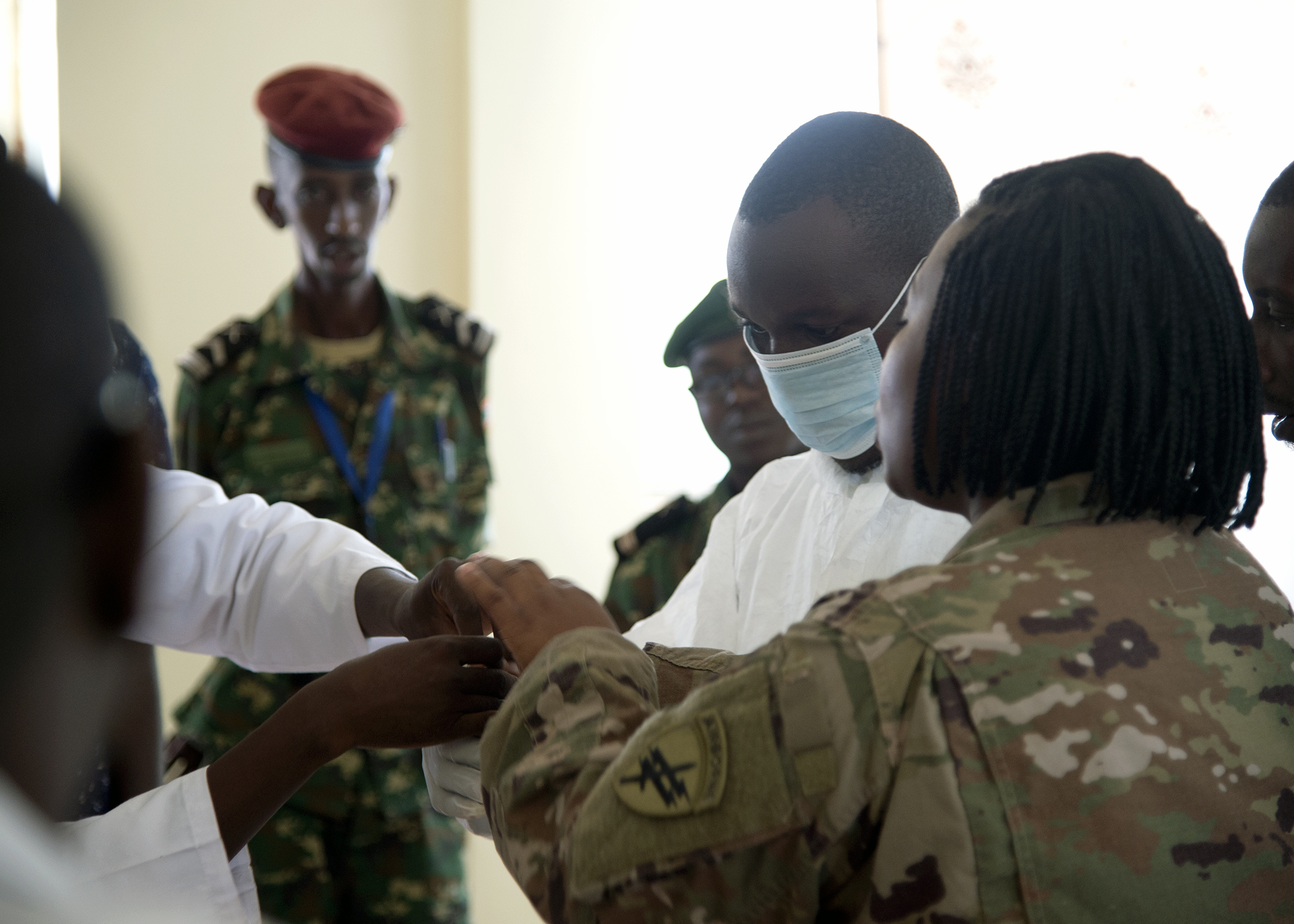 U.S. Army Maj. Lakesha Williams, right, public health nurse for the 403rd Civil Affairs Battalion, assigned to Combined Joint Task Force-Horn of Africa (CJTF-HOA), assists hospital personnel with the donning of a hazardous material suit during a presentation at the Kamenge Military Hospital, Bujumbura, Burundi, June 18, 2019. The 403rd Civil Affairs Battalion, CJTF-HOA, and military personnel and doctors from the Kamenge Military Hospital conducted an Ebola preparedness subject matter expert exchange as a precautionary measure for personnel near the border of the Democratic Republic of Congo. (U.S. Navy photo by Mass Communication Specialist 1st Class Nick Scott)