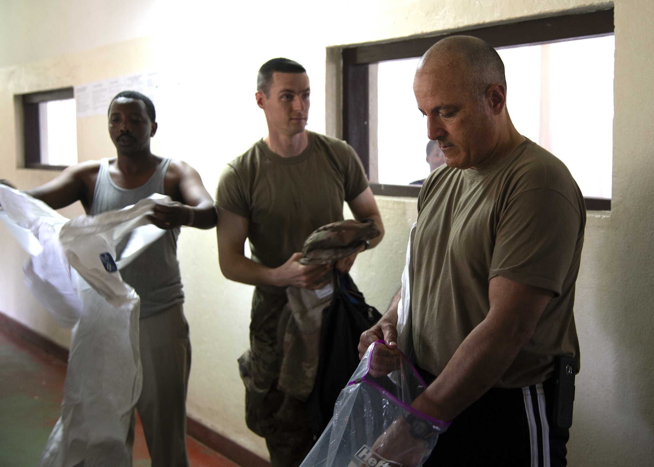 U.S. Air Force Col. James Bermudez, right, force surgeon assigned to Combined Joint Task Force-Horn of Africa (CJTF-HOA); U.S. Army Capt. William Brant, center, team chief for the 403rd Civil Affairs Battalion, assigned to CJTF-HOA; and Burundi National Defence Force Maj. Jerome Irankunda, left, microbiologist and chief of laboratory services at the Kamenge Military Hospital, practice the donning of hazardous material suits at the Kamenge Military Hospital, Bujumbura, Burundi, June 20, 2019. The 403rd Civil Affairs Battalion, CJTF-HOA, and military personnel and doctors from the Kamenge Military Hospital conducted an Ebola preparedness subject matter expert exchange as a precautionary measure for personnel near the border of the Democratic Republic of Congo. (U.S. Navy photo by Mass Communication Specialist 1st Class Nick Scott)