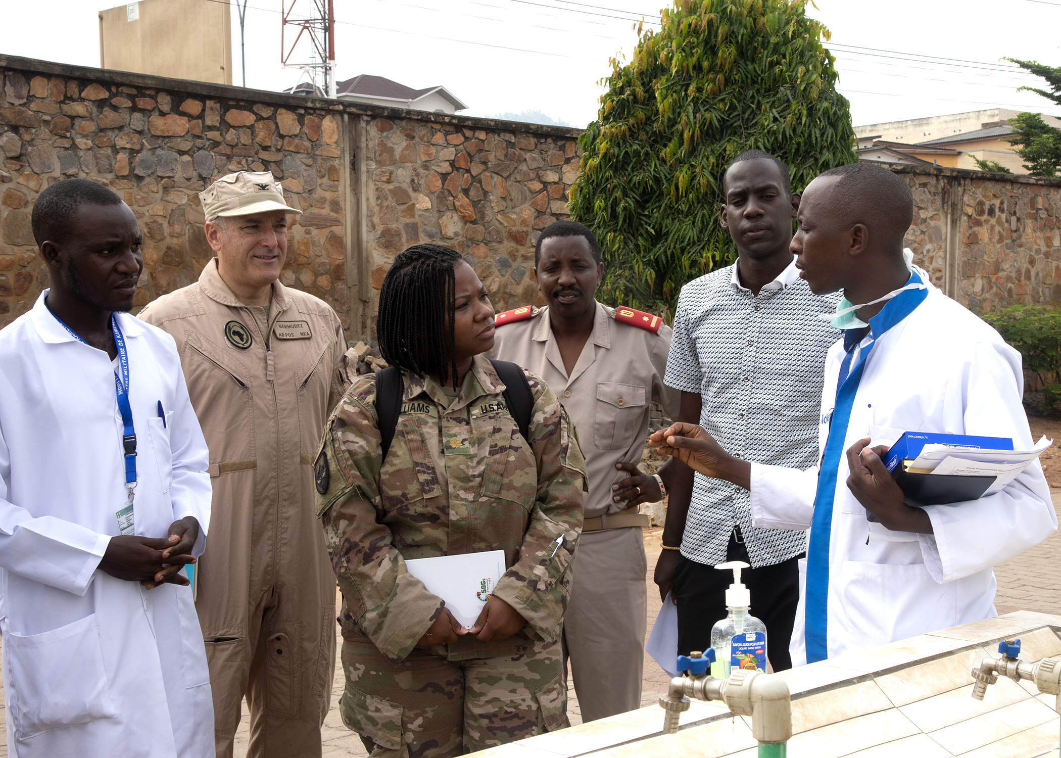 U.S. Air Force Col. James Bermudez, center left, force surgeon assigned to Combined Joint Task Force-Horn of Africa (CJTF-HOA), and U.S. Army Maj. Lakesha Williams, center, public health nurse for the 403rd Civil Affairs Battalion, assigned to CJTF-HOA, speak with Simbaraizye Deo, a doctor and chief of emergency services at Kamenge Military Hospital, as he demonstrates one of the hand washing stations at the Kamenge Military Hospital, Bujumbura, Burundi, June 17, 2019. The 403rd Civil Affairs Battalion, CJTF-HOA, and military personnel and doctors from the Kamenge Military Hospital conducted an Ebola preparedness subject matter expert exchange as a precautionary measure for personnel near the border of the Democratic Republic of Congo. (U.S. Navy photo by Mass Communication Specialist 1st Class Nick Scott)