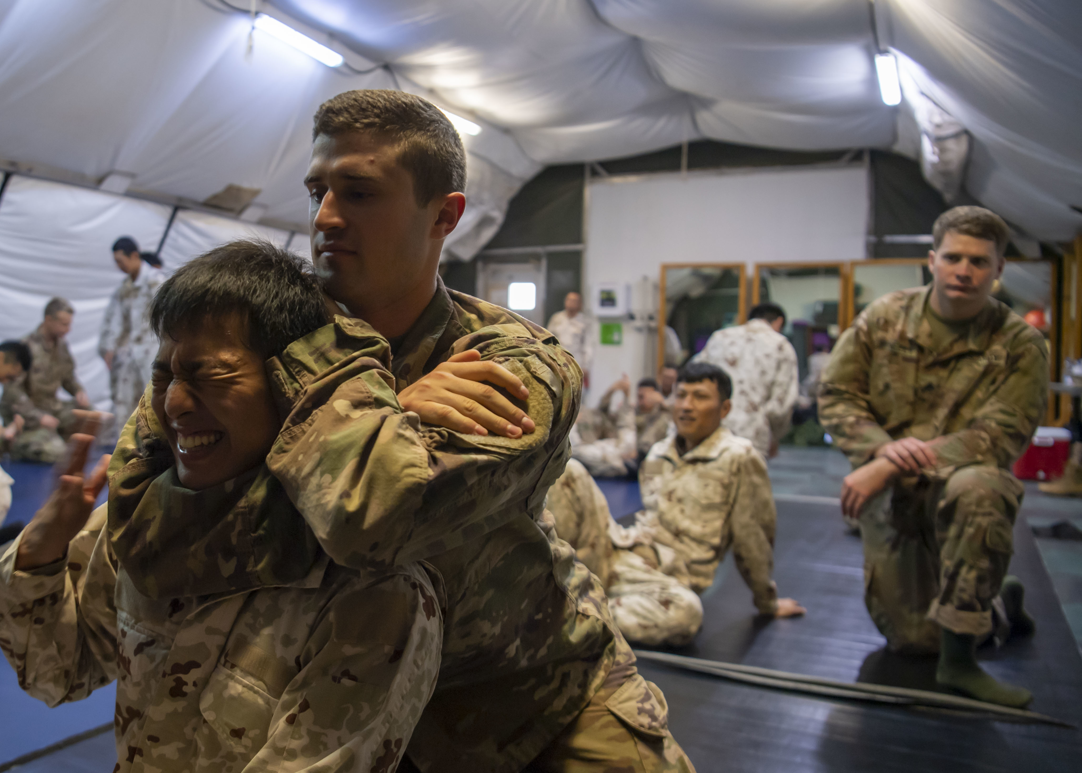 U.S. Army 1st Lt. Joseph Presti, platoon leader 101st Division, 1st Battalion, 26th Infantry Regiment, Task Force Warrior, assigned to Combined Joint Task Force-Horn of Africa (CJTF-HOA), practices a rear-naked choke with a Japanese Ground Self-Defense Force (JGSDF) soldier during a combatives exchange at Camp Lemonnier, Djibouti, July 1, 2019. The purpose of the joint exchange was to share Japanese combative techniques and forge relationships between CJTF-HOA and JGSDF. (U.S. Air Force photo by Staff Sgt. J.D. Strong II)