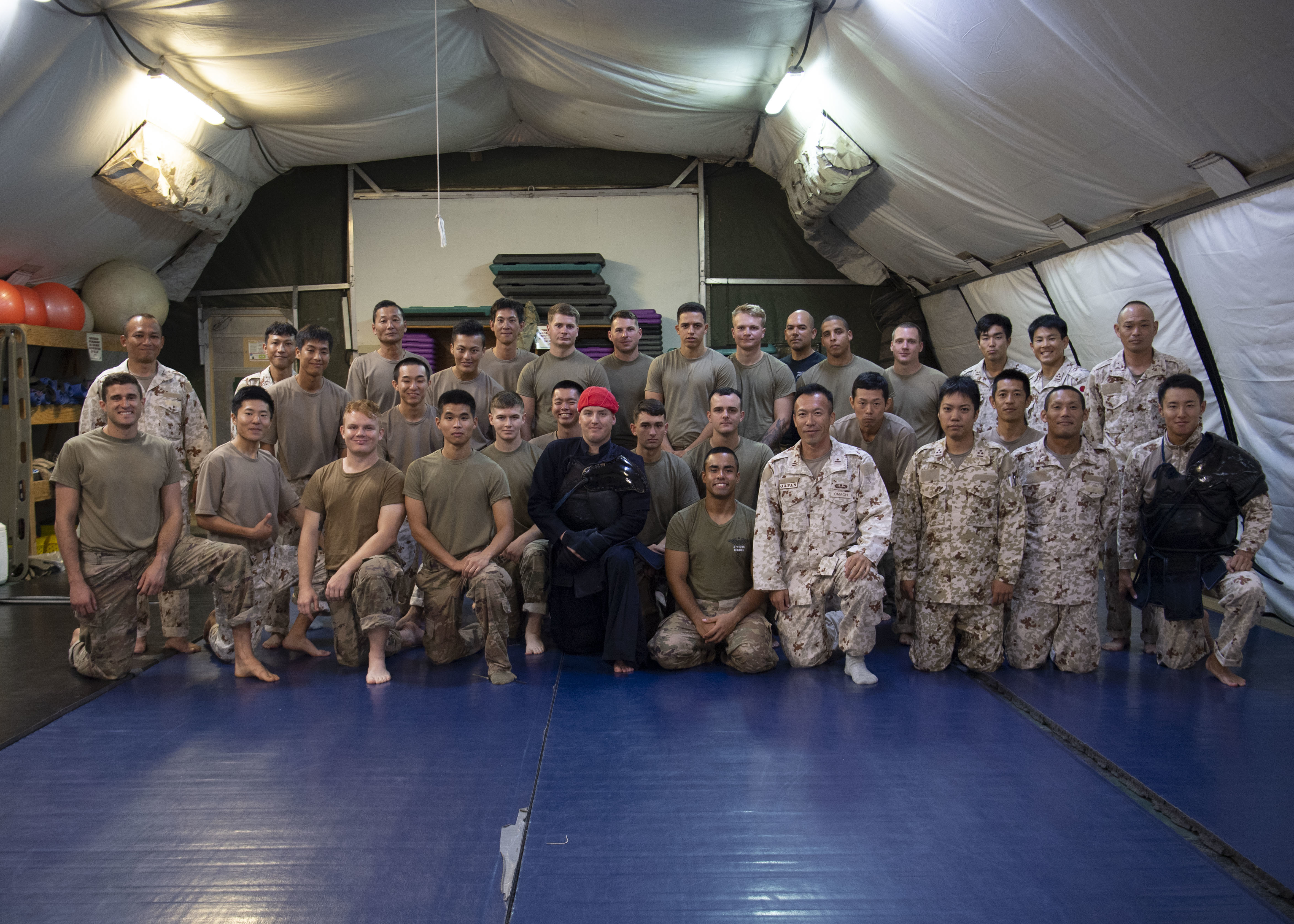 U.S. Army Soldiers assigned to Combined Joint Task Force-Horn of Africa (CJTF-HOA) and Japanese Ground Self-Defense Force (JGSDF) soldiers pose for a group photo after a combatives exchange at Camp Lemonnier, Djibouti, July 1, 2019. The purpose of the joint exchange was to share Japanese combative techniques and forge relationships between CJTF-HOA and the JGSDF. (U.S. Air Force photo by Staff Sgt. J.D. Strong II) (U.S. Air Force photo by Staff Sgt. J.D. Strong II)