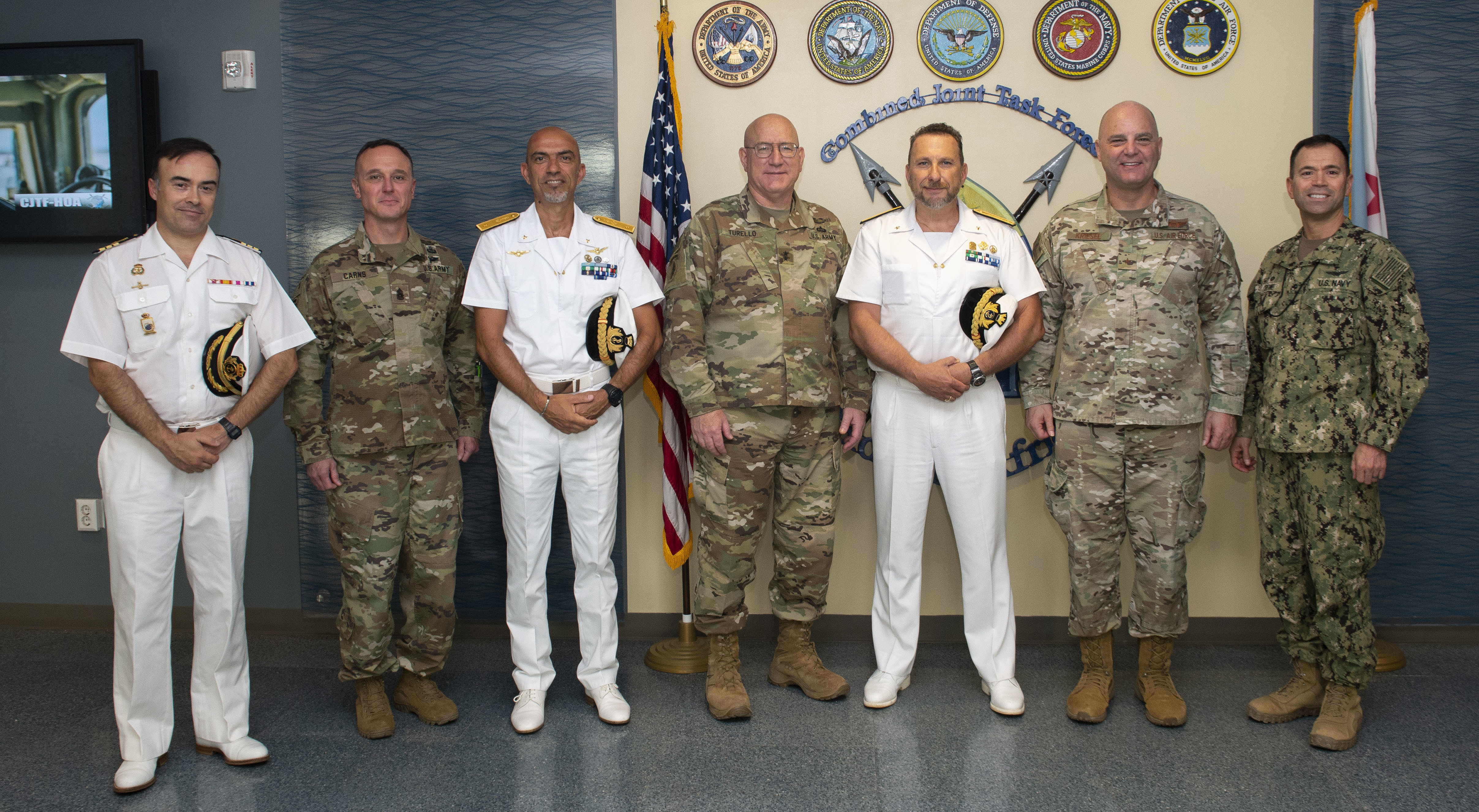 U.S. Army Maj. Gen. Michael Turello, commanding general, Combined Joint Task Force-Horn of Africa (CJTF-HOA), center, poses for a photo with Italian Rear Adm. Giovanni Piegaja, deputy operation commander, Operation Atalanta, center right, and other service members from CJTF-HOA, Camp Lemonnier and Operation Atalanta at Camp Lemonnier, Djibouti, July 21, 2019. Piegaja and members of his staff visited CJTF-HOA to discuss the Atalanta mission and strengthen the partnership between CJTF-HOA and Operation Atalanta. (U.S. Air Force photo by Senior Airman Gabrielle Spalding)