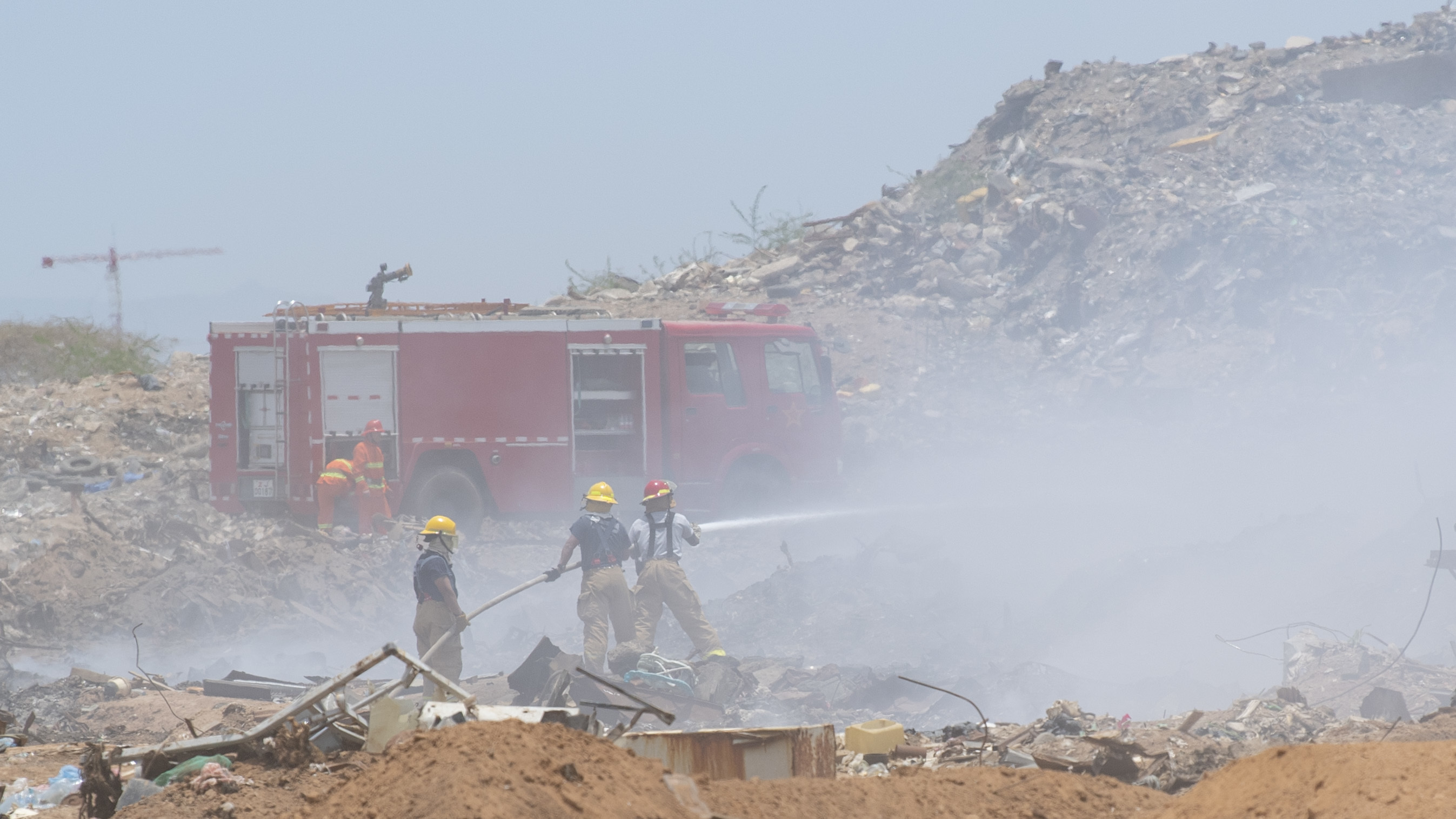Camp Lemonnier Fire and Emergency Services firefighters use a hose to extinguish a fire alongside Chinese firefighters at Douda landfill in Djibouti, Aug. 14, 2019.  At the request of the government of Djibouti and in support of the U.S. Embassy Djibouti, Combined Joint Task Force-Horn of Africa engineers worked alongside Camp Lemonnier, Djiboutian, French and Chinese firefighters to help stop a fire at the landfill from spreading. (U.S. Air Force photo by Staff Sgt. J.D. Strong II)