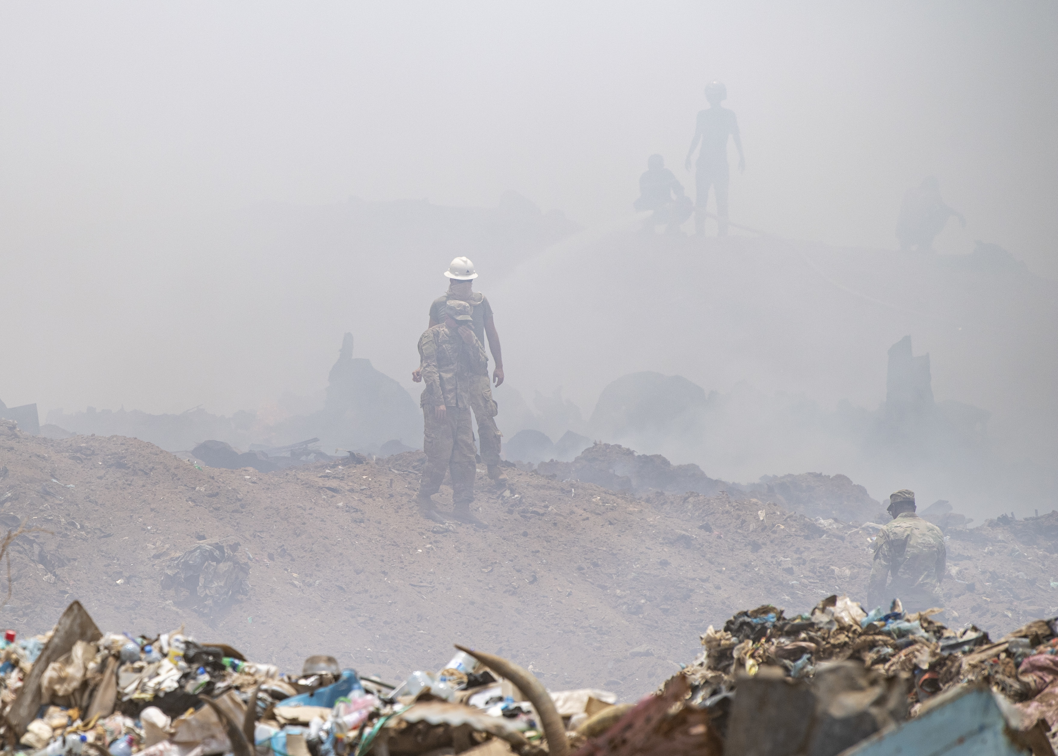 U.S. Army Soldiers from 465th Engineer Company, 926th Engineer Battalion, 926th Engineer Brigade, 412th Theater Engineer Command, based in Birmingham, Alabama, assigned to Combined Joint Task Force-Horn of Africa, assess their firefighting sector at the Douda landfill in Djibouti, Aug. 14, 2019. During a fire at the landfill, the 465th used bulldozers to create dirt berms that would make firebreaks and stop the flames from spreading outward. (U.S. Air Force photo by Staff Sgt. J.D. Strong II)