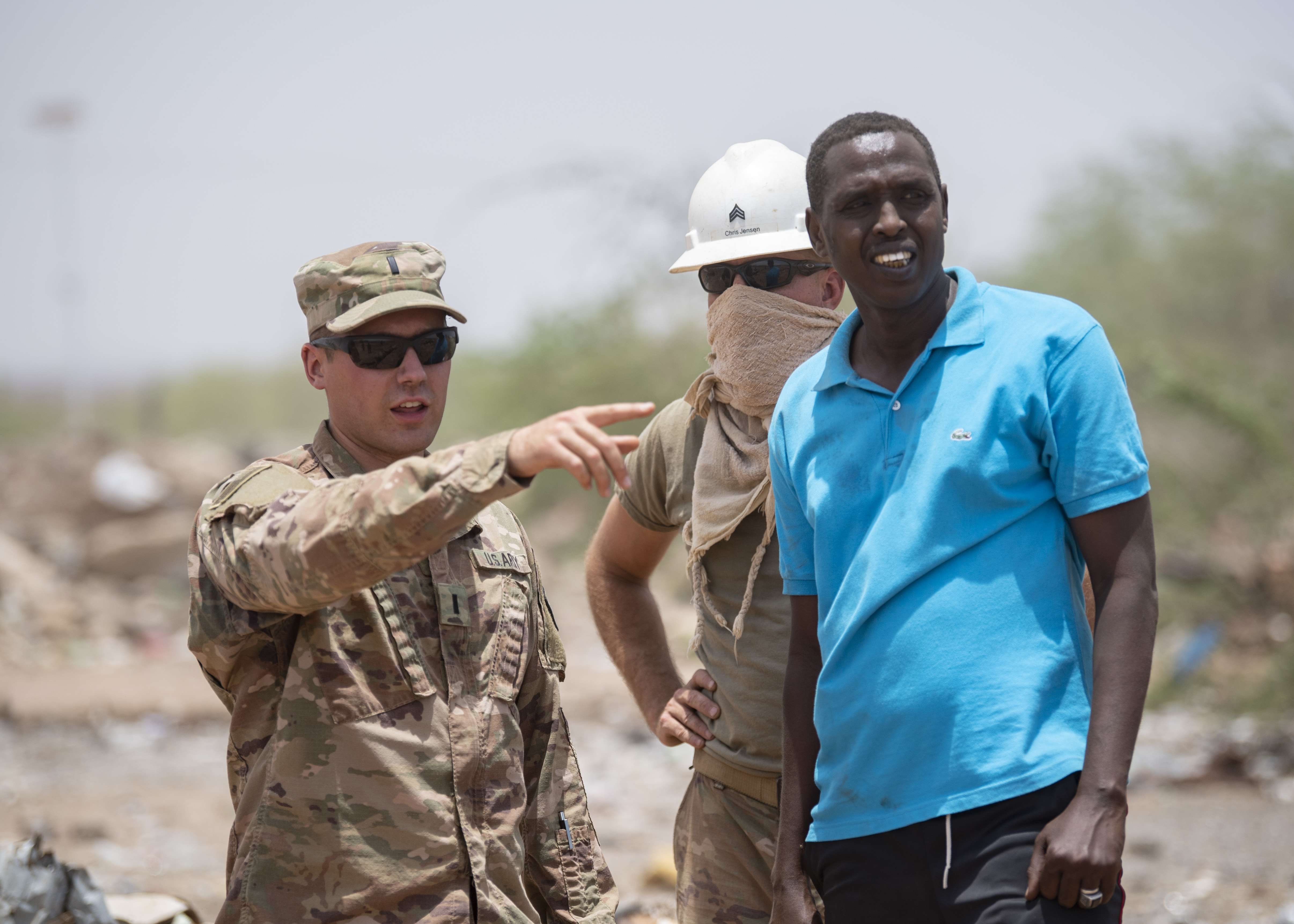 U.S. Army 1st Lt. Daniel Csakai, platoon leader, 465th Engineer Company, 926th Engineer Battalion, 926th Engineer Brigade, 412th Theater Engineer Command, based in Birmingham, Alabama, assigned to Combined Joint Task Force-Horn of Africa, speaks with a Djibouti Fire Brigade firefighter about the firefighting efforts at Douda landfill in Djibouti, Aug. 14, 2019. During a fire at the landfill, the 465th used bulldozers to create dirt berms that would make firebreaks and stop the flames from spreading outward. (U.S. Air Force photo by Staff Sgt. J.D. Strong II)