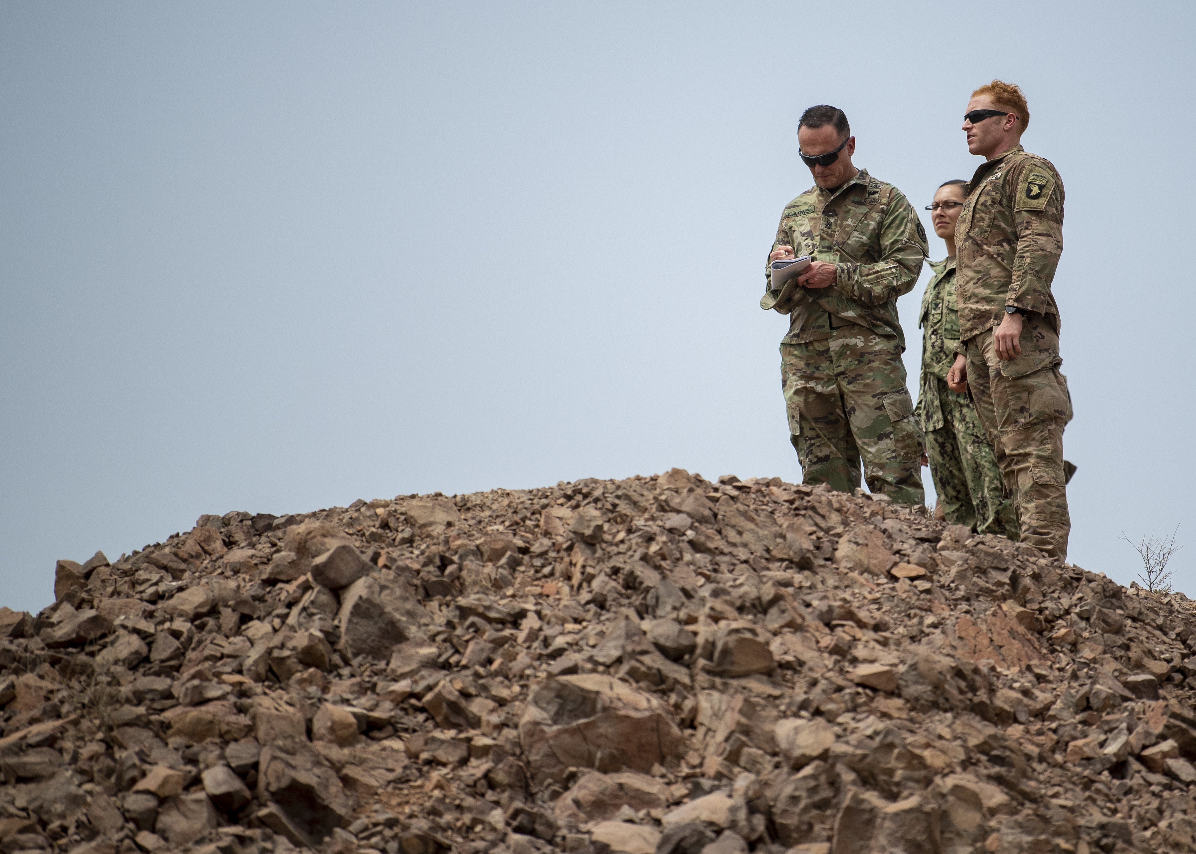 U.S. Army Command Sgt. Maj. Shawn Carns, command senior enlisted leader (SEL), Combined Joint Task Force-Horn of Africa (CJTF-HOA), takes notes while being briefed by U.S. Army First Lt. Nicholas Noga, platoon leader, 101st Division, 1st Battalion, 26th Infantry Regiment, Task Force Warrior, assigned to CJTF-HOA, during his battlefield circulation visit at Arta Range, Djibouti, Aug. 26, 2019. Battlefield circulation visits allow Carns to meet with units within CJTF-HOA's combined joint operations area for familiarization and rapport-building. (U.S. Air Force photo by Staff Sgt. J.D. Strong II)