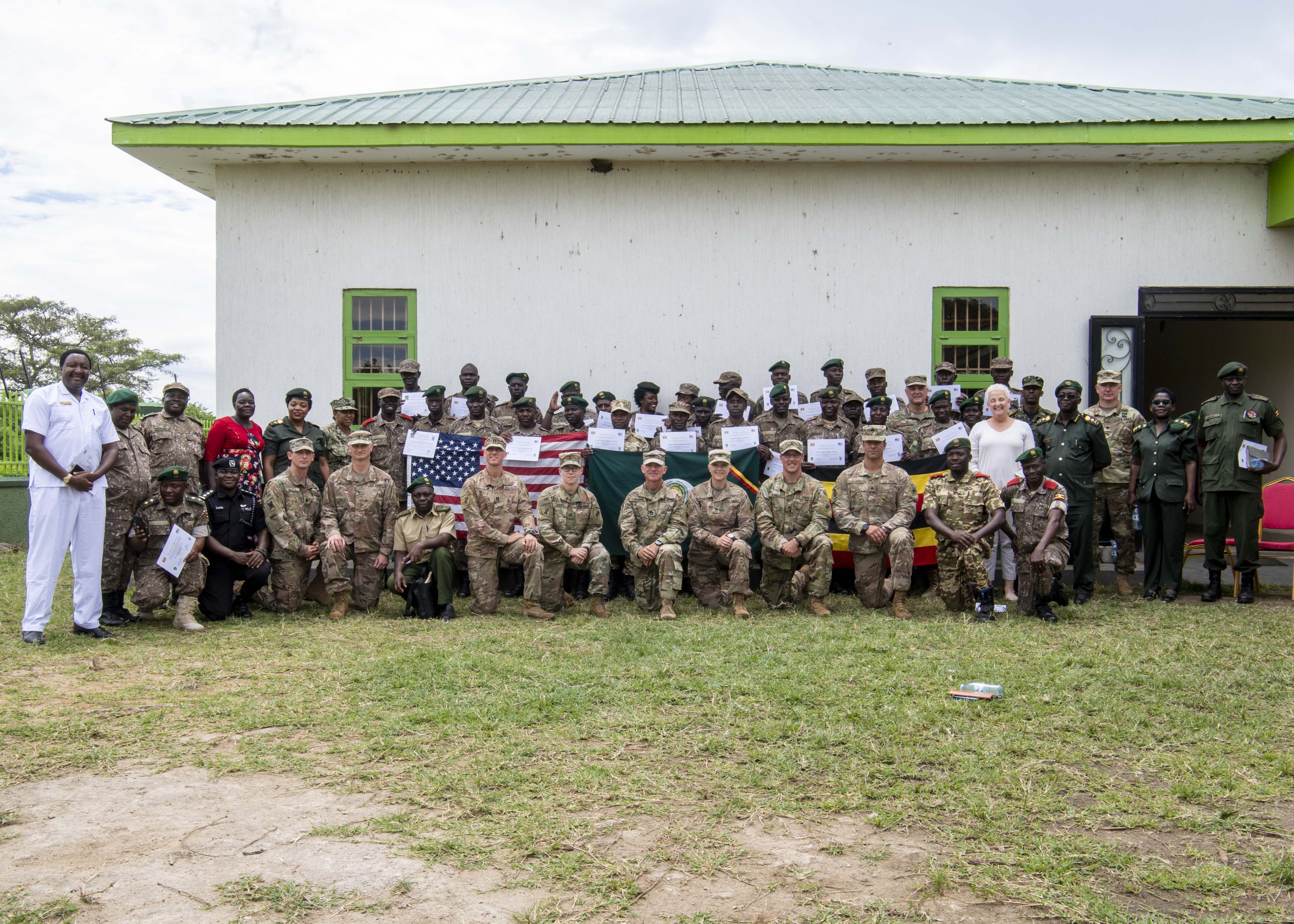 U.S. Ambassador to Uganda Deborah R. Malac; U.S. Air Force Brig. Gen. James R. Kriesel, deputy commanding general of Combined Joint Task Force-Horn of Africa (CJTF-HOA); and Sam Mwandha, executive director of Uganda Wildlife Authority, pose for a group photo with Counter Illicit Trafficking Junior Leadership Course graduates and Ugandan supporters at Queen Elizabeth Park, Uganda, Oct. 10, 2019. Twenty-five UWA Rangers graduated the course. (U.S. Air Force photo by Staff Sgt. J.D.  Strong II)