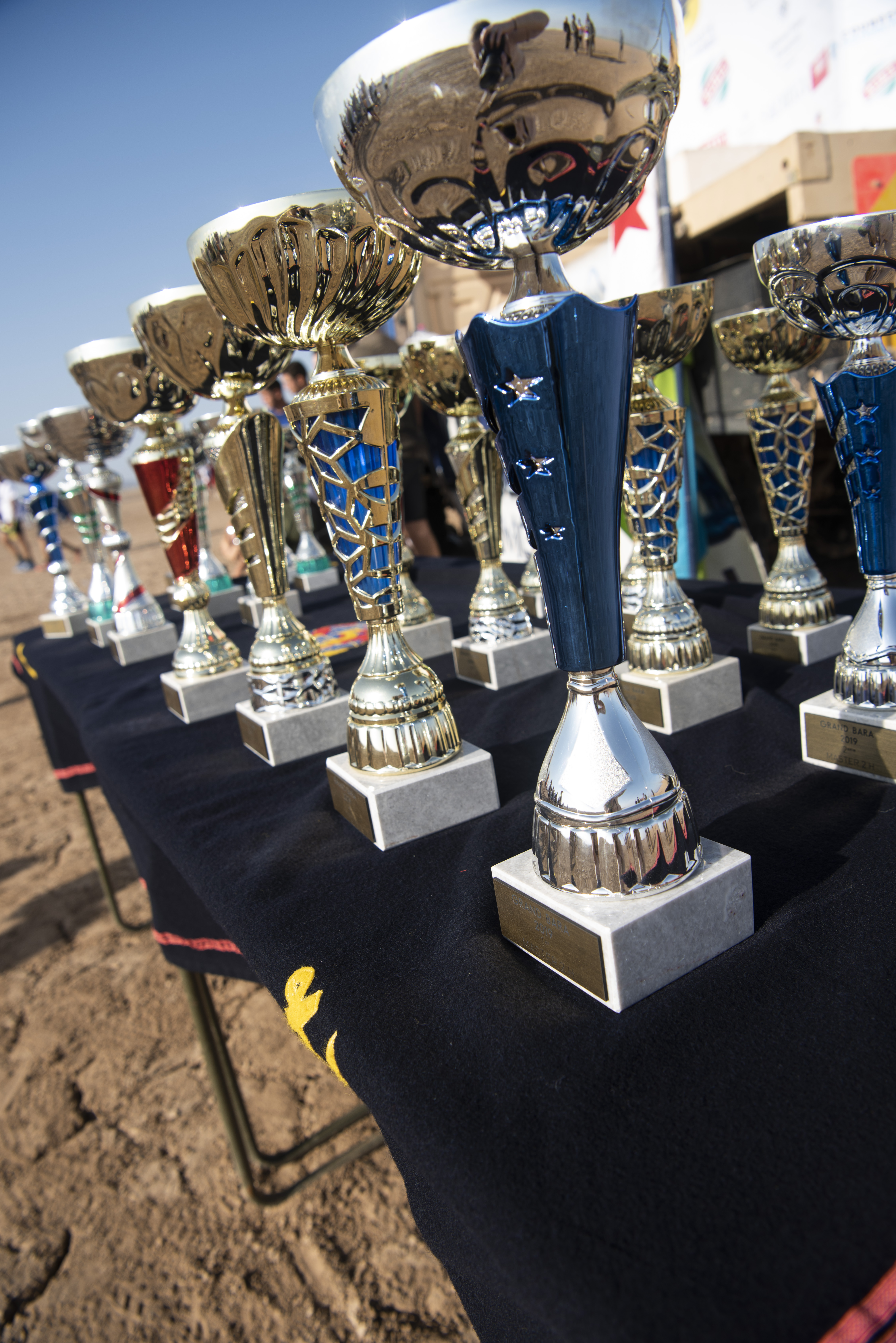 Trophies for winners of the annual Grand Bara Race are displayed before the closing ceremony in the Grand Bara Desert, Jan. 15, 2020. The first place male winner represented the Djiboutian Republican Guard and completed the 15k race in approximately 43 minutes. The first place female winner also represented the Djiboutian Republican Guard and completed the race in approximately 53 minutes. (U.S. Air Force photo by Tech. Sgt. Ashley Nicole Taylor)