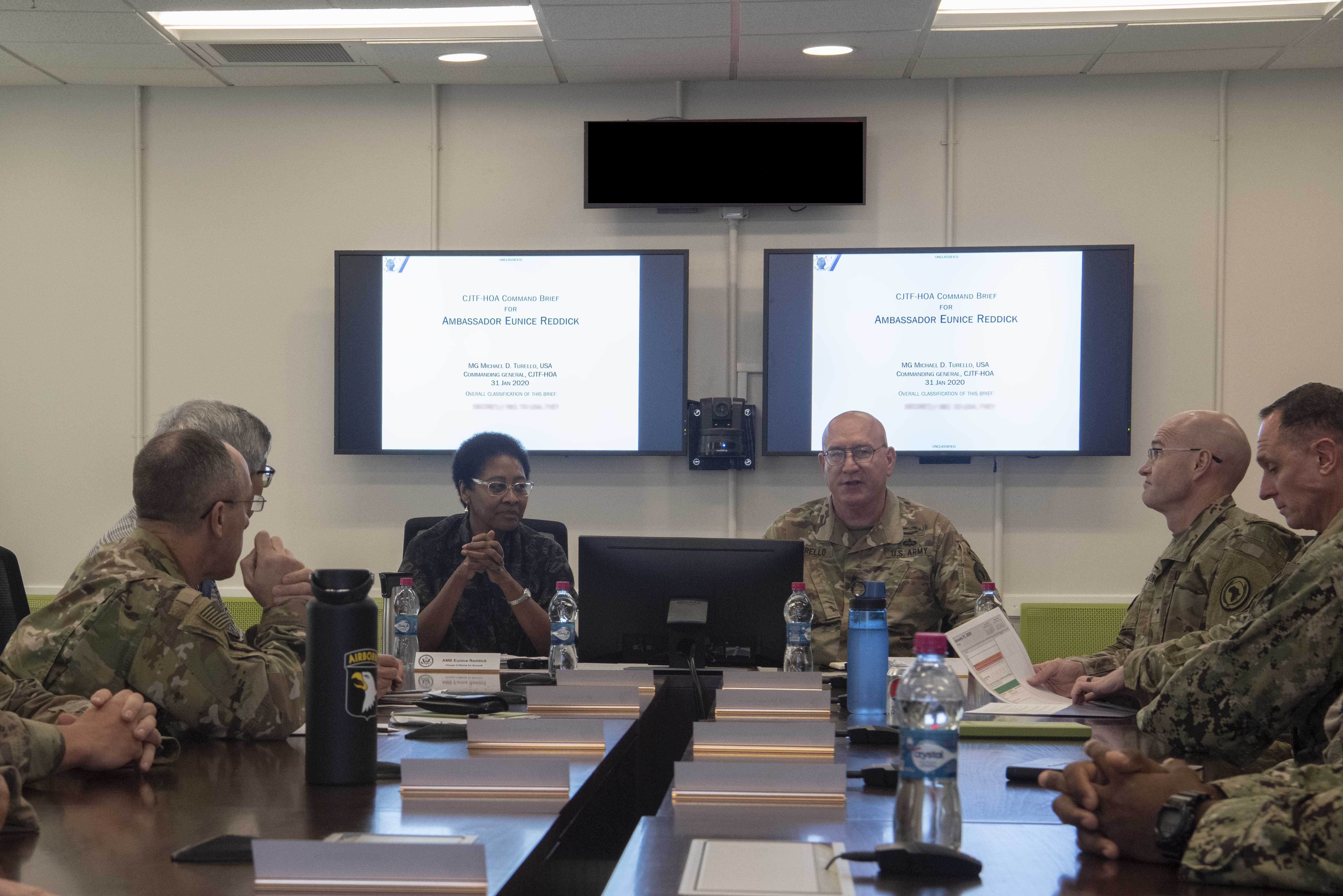 Key leaders from Combined Joint Task Force- Horn of Africa (CJTF-HOA), brief Ambassador Eunice S. Reddick, Chargé d'affaires of the U.S. Embassy to Burundi, at Camp Lemonnier, Djibouti, Jan. 31, 2020. Reddick visited to learn more about the CJTF-HOA mission. (U.S. Air Force photo illustration by Tech. Sgt. Ashley Nicole Taylor)